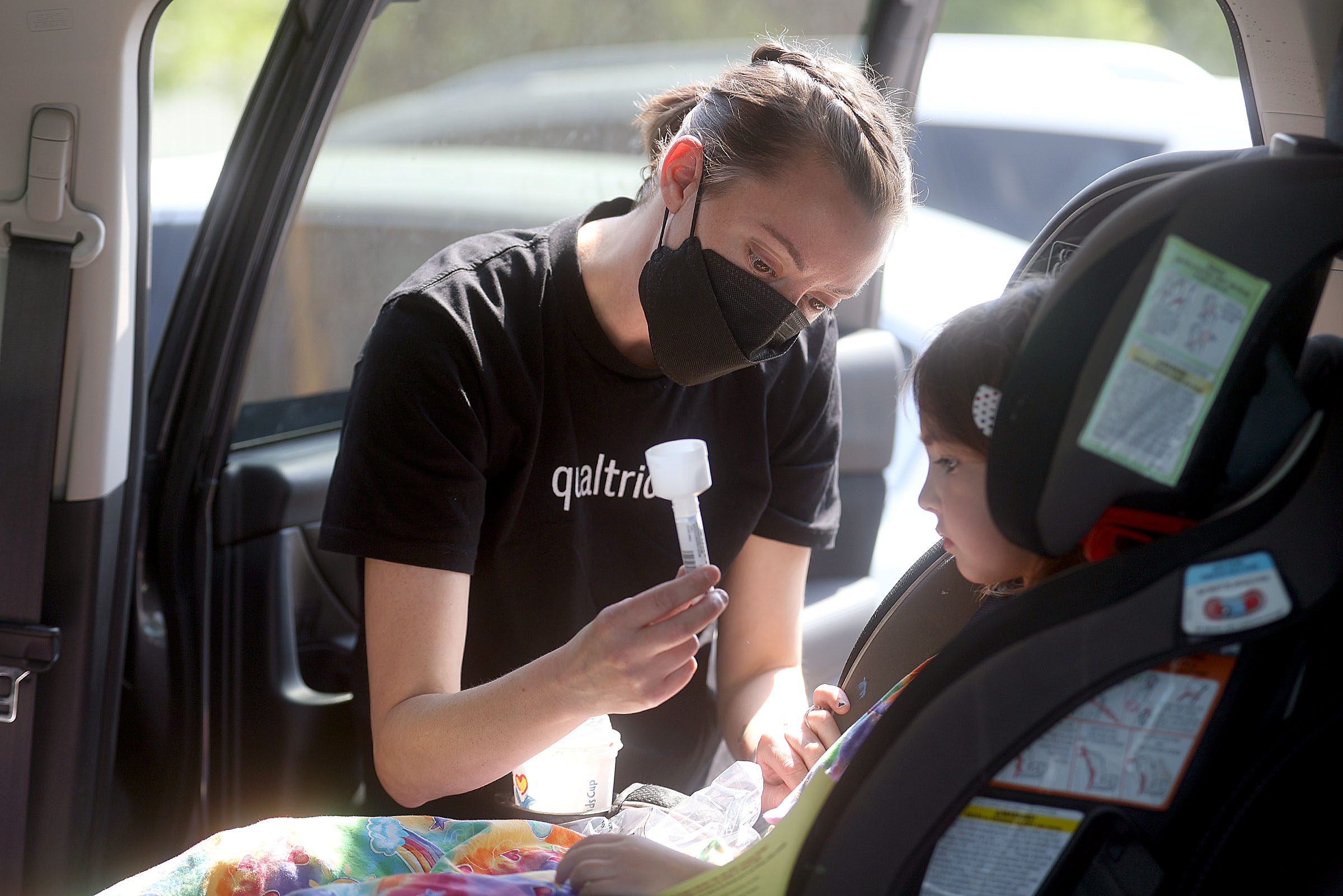 Catherine Jeppsen helps her daughter as she attempts to collect saliva for a COVID-19 test.