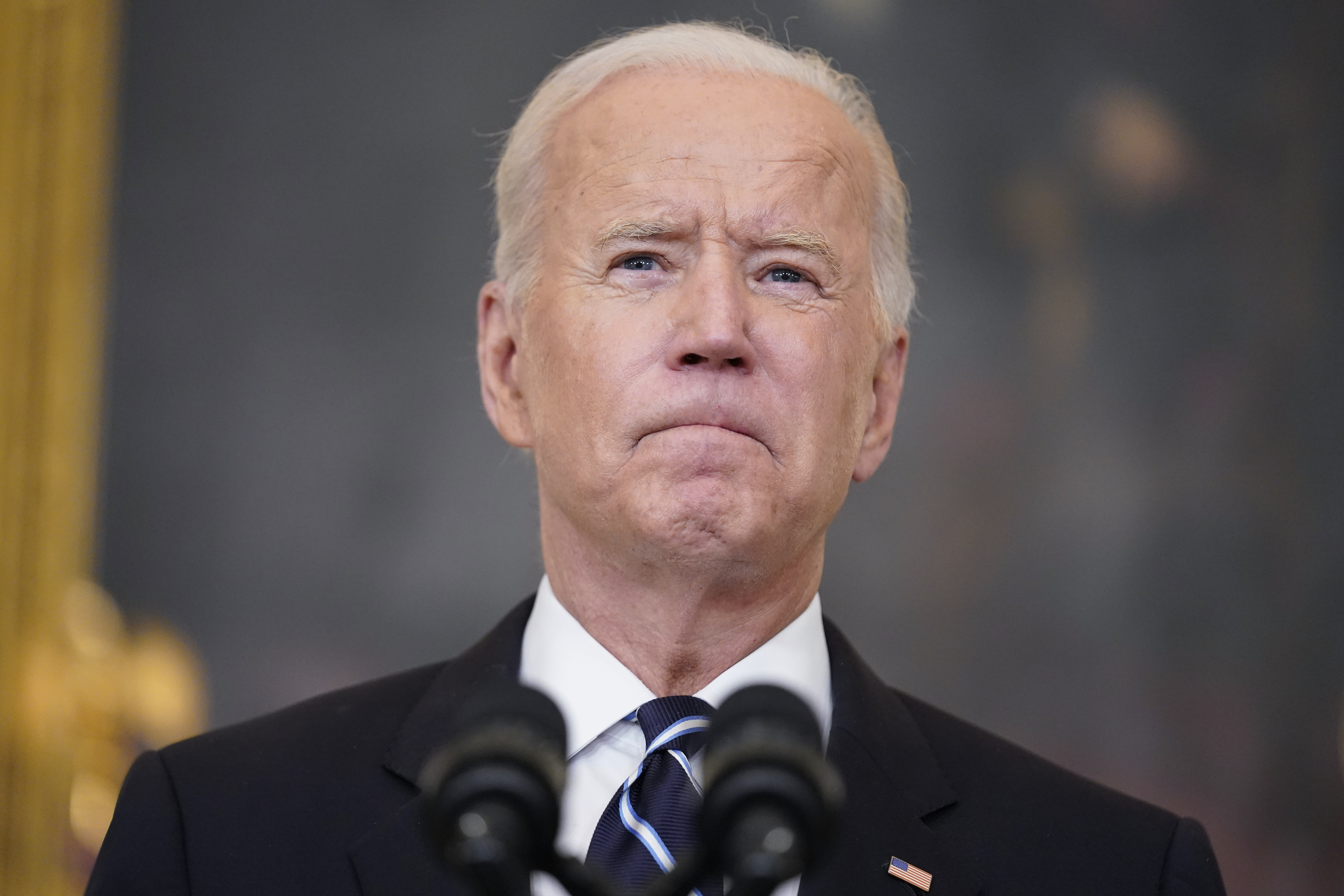 President Joe Biden pauses as he speaks in the State Dining Room at the White House.
