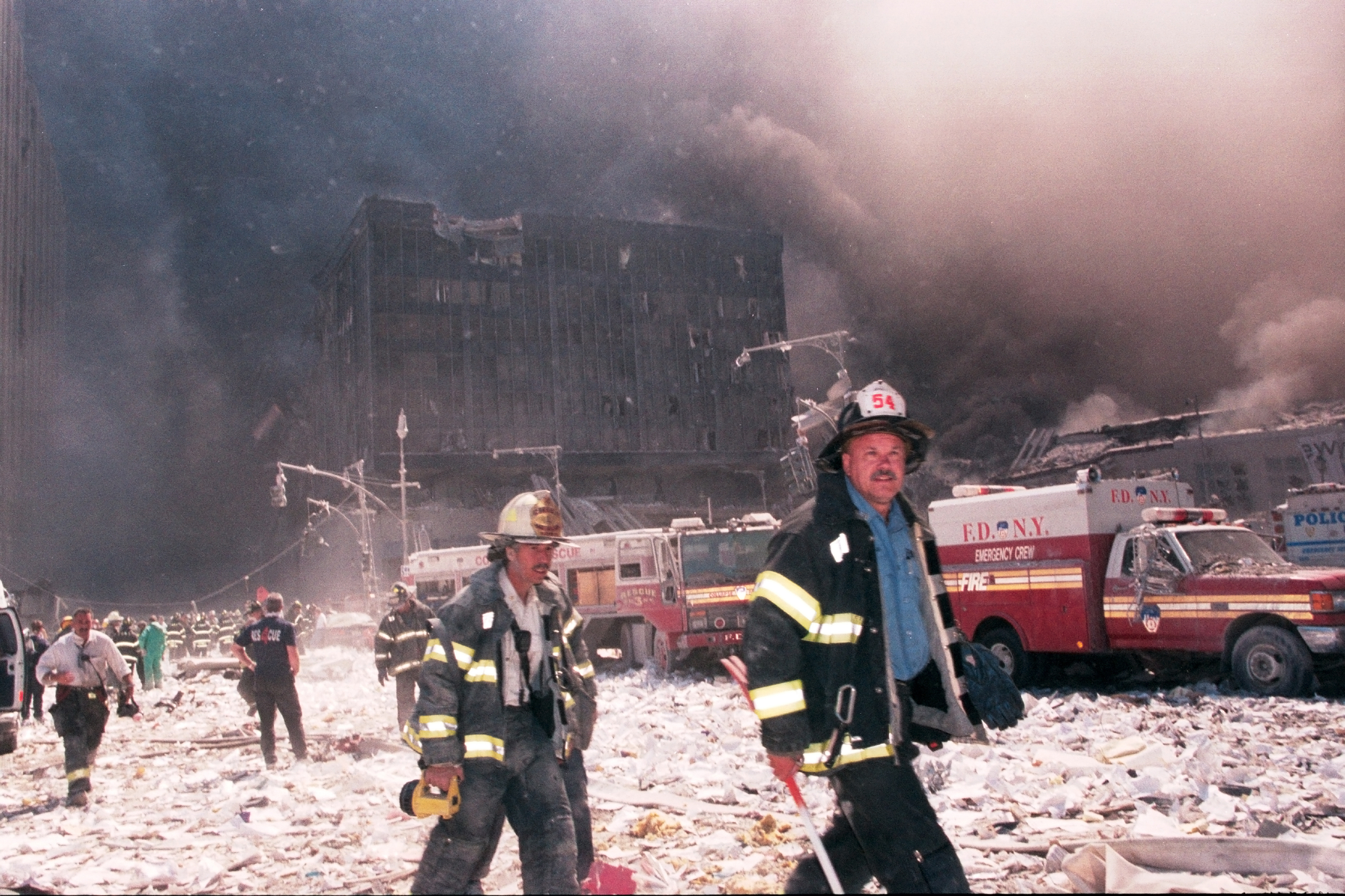 Firefighters walk through Ground Zero in the aftermath of the World Trade Center collapse on Sept 11th, 2001