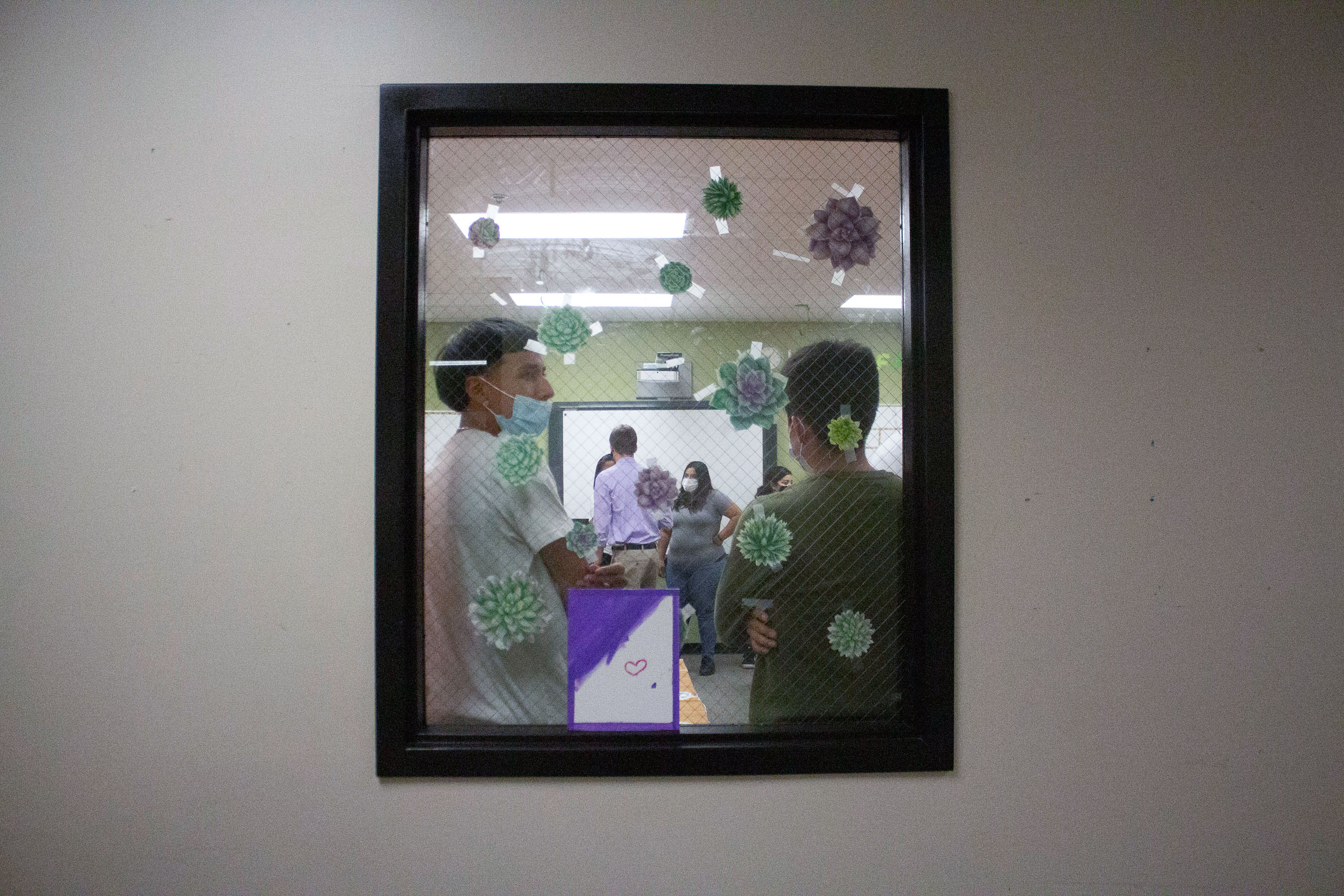 Two students are framed by a window decorated with decals. One student wears a blue face mask.
