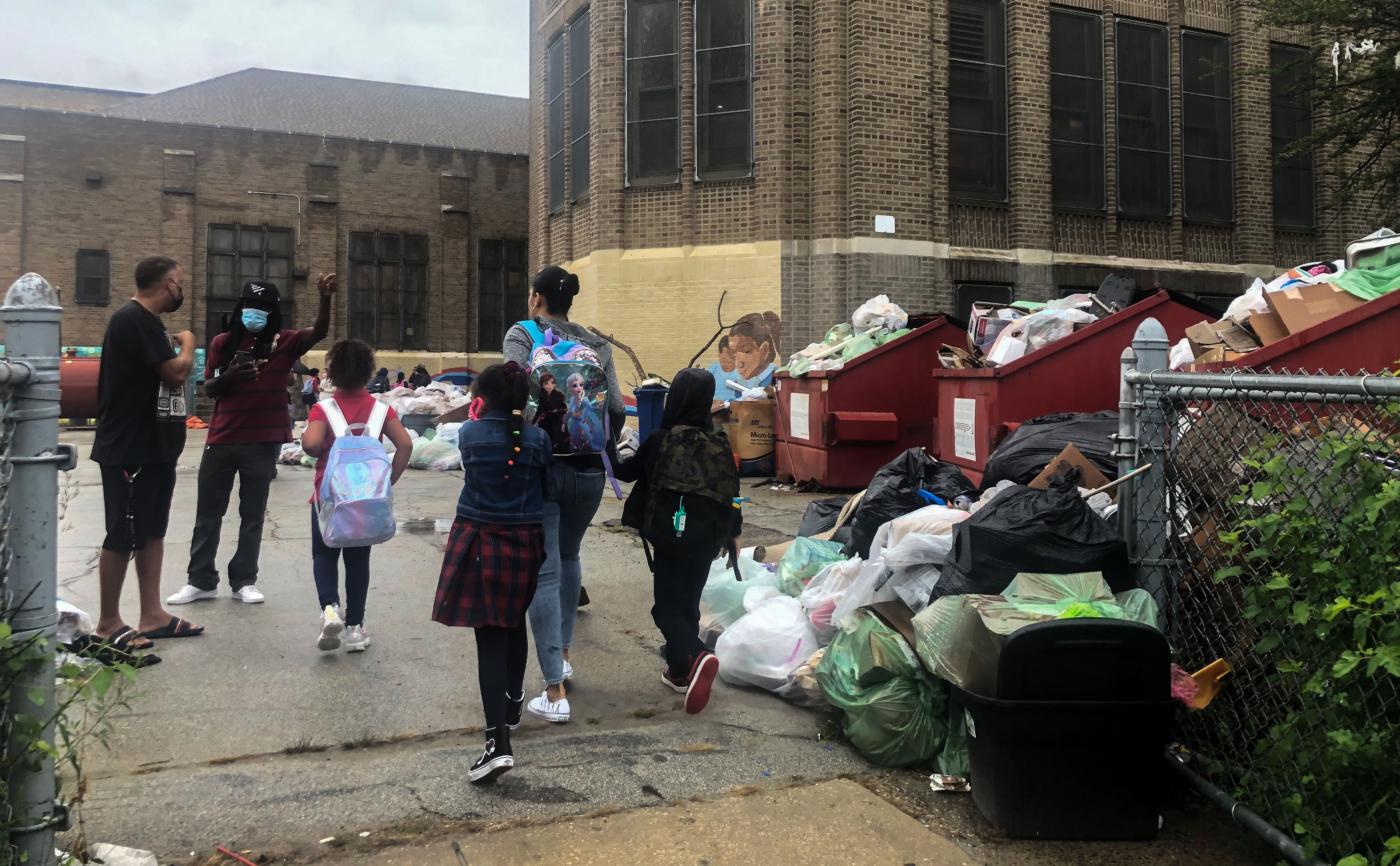 Children and adults were dark clothing walk past clear and brown colored trash bags.