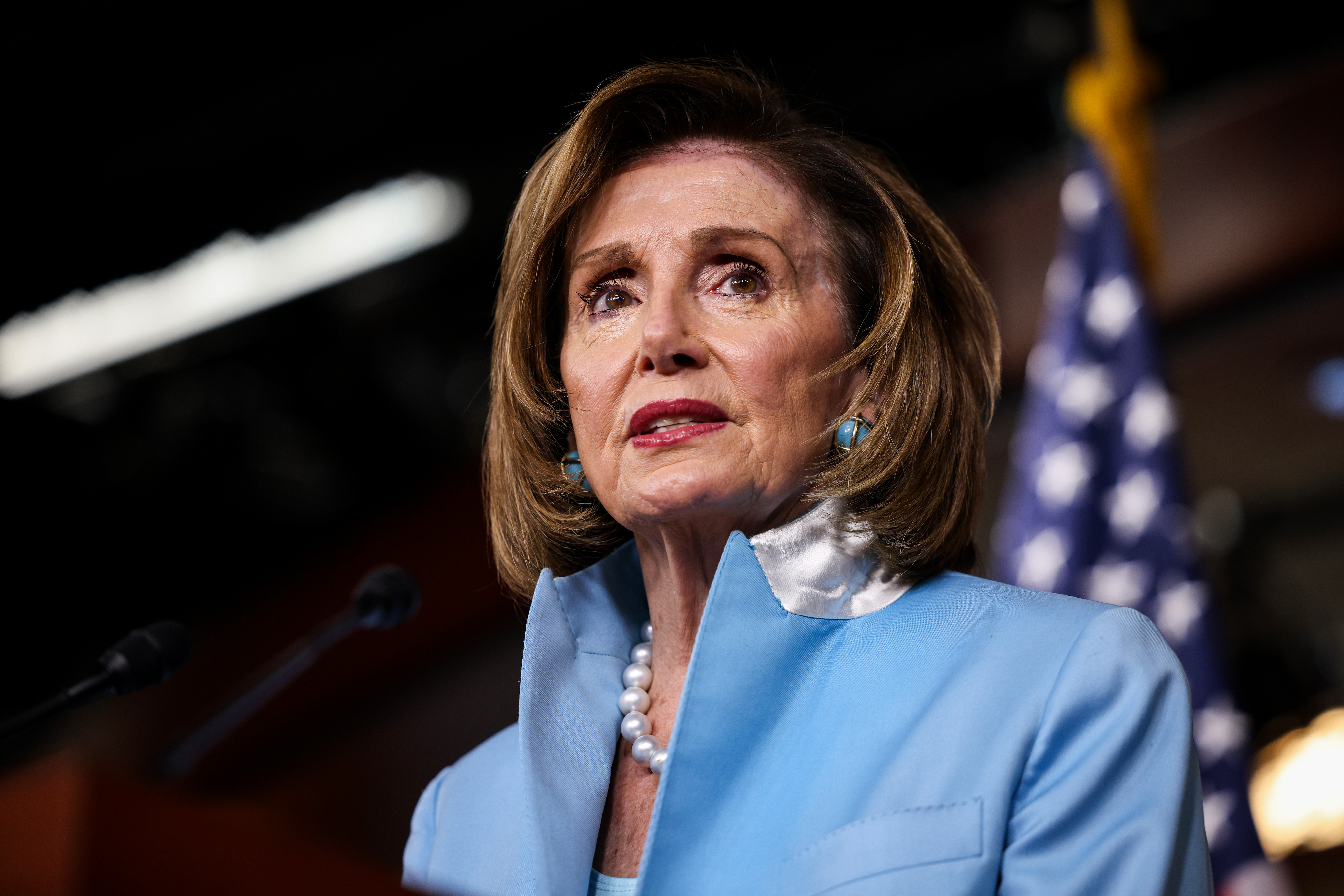 Nancy Pelosi in a light blue jacket looking into the distance with a U.S. flag behind her.