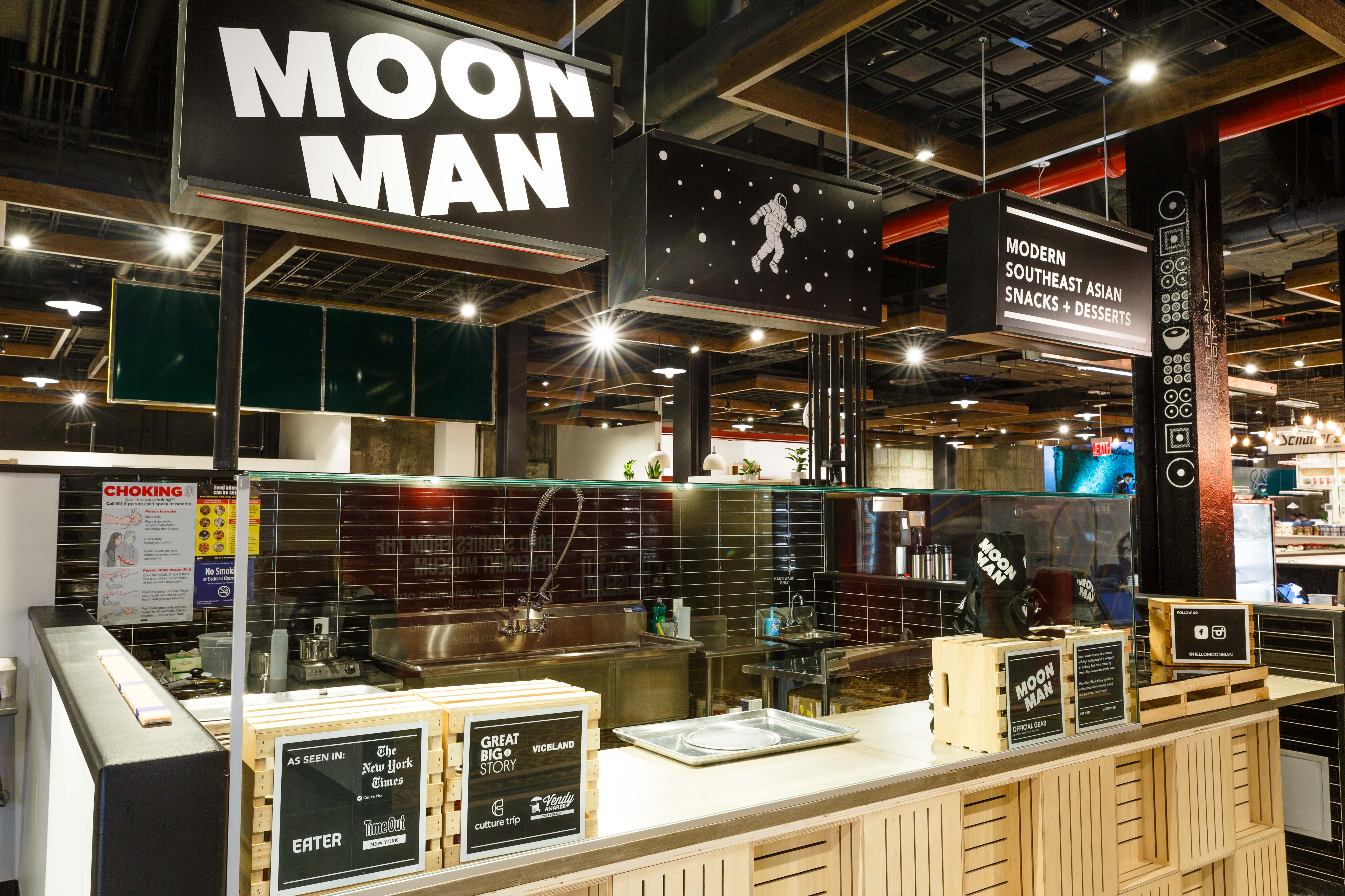 """A black sign displays """"Moon Man"""" with white lettering."""