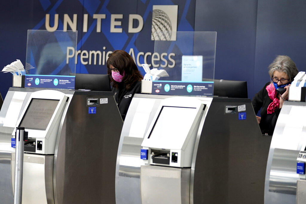 United Airlines employees work at ticket counters at O'Hare International Airport in Chicago.