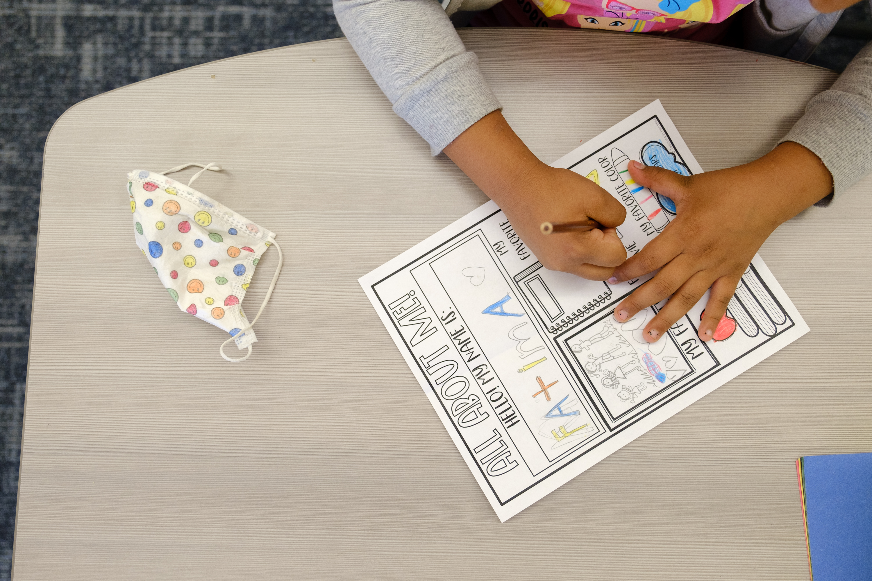 A mask sits next to a student as they complete a worksheet. The photo is zoomed in on the worksheet and the student's hands.