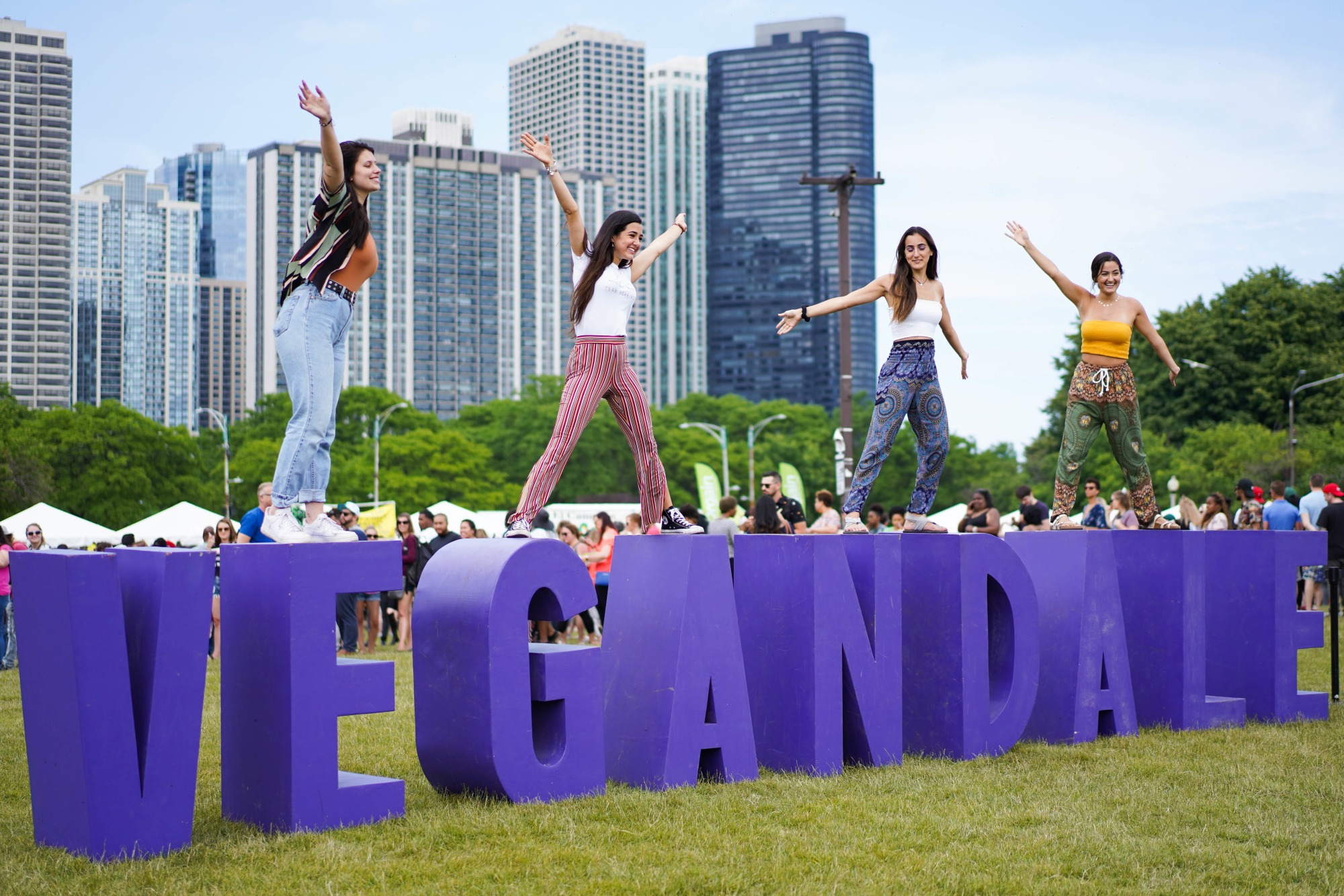 """Large purple letters spelling """"Vegandale"""" in the park with people on top."""