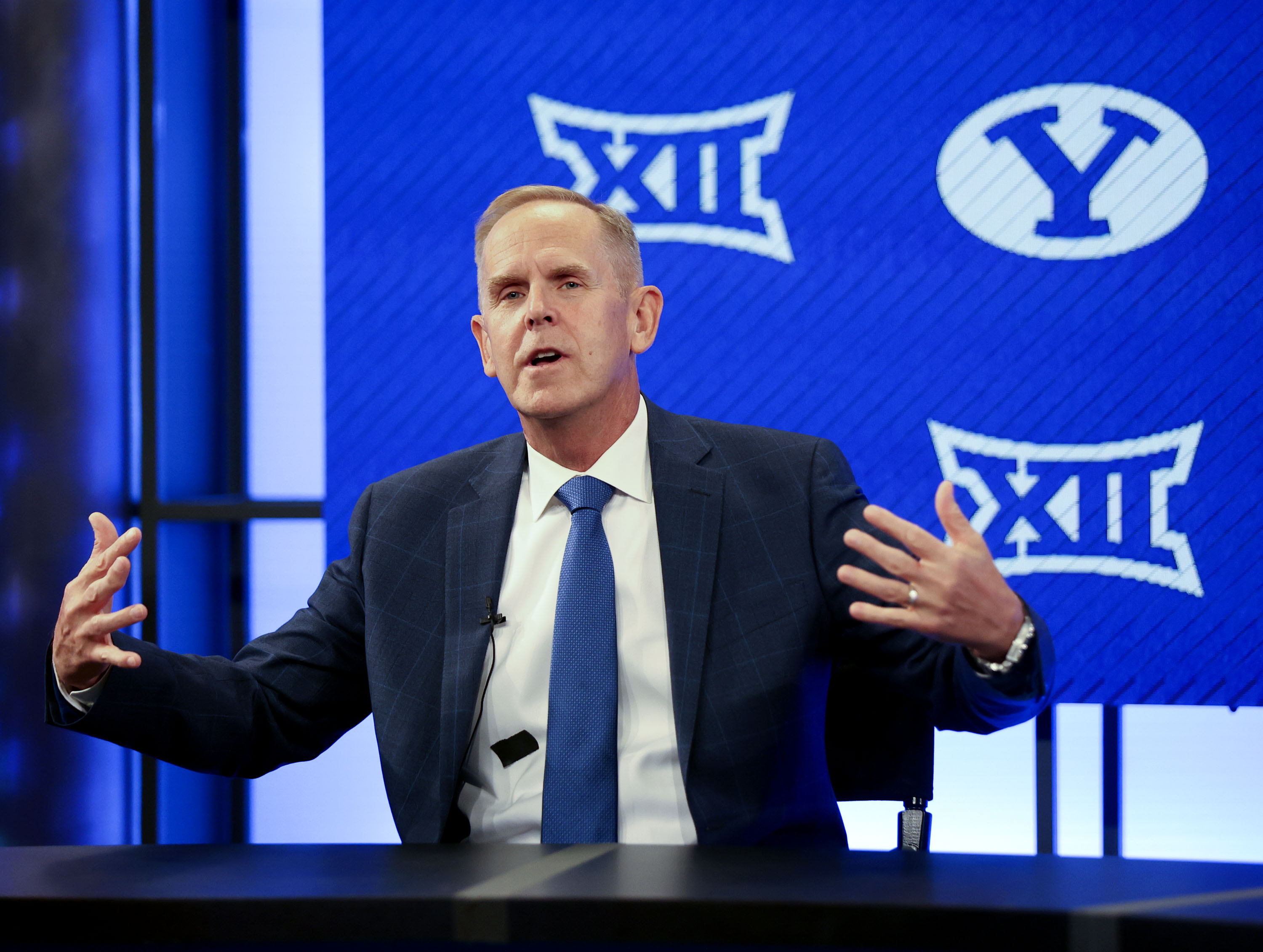 BYU athletic director Tom Holmoe gestures while announcing that BYU has accepted an invitation to the Big 12 Conference.