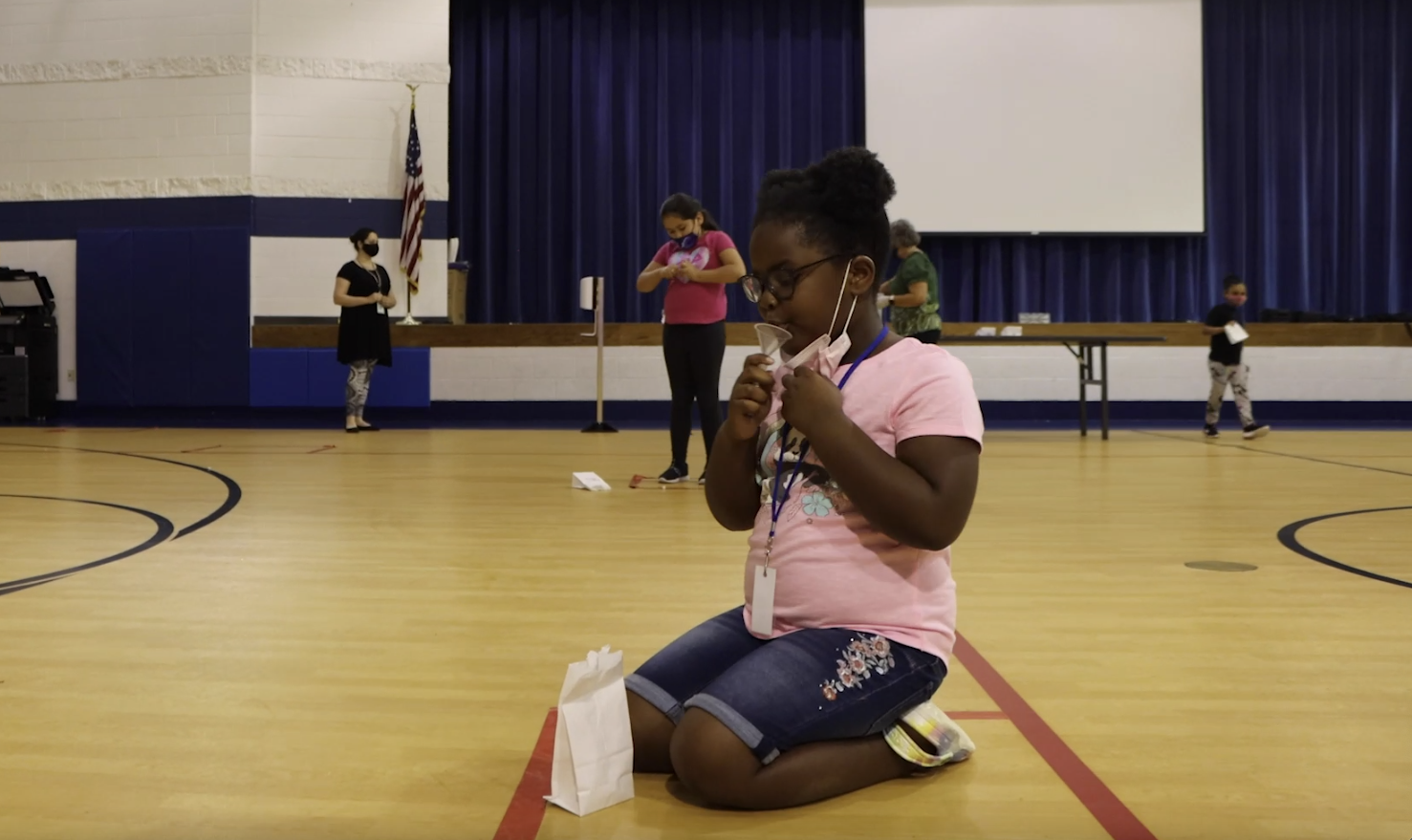 A young girl produces a saliva sample for a SHIELD COVID test inside of a large gymnasium.