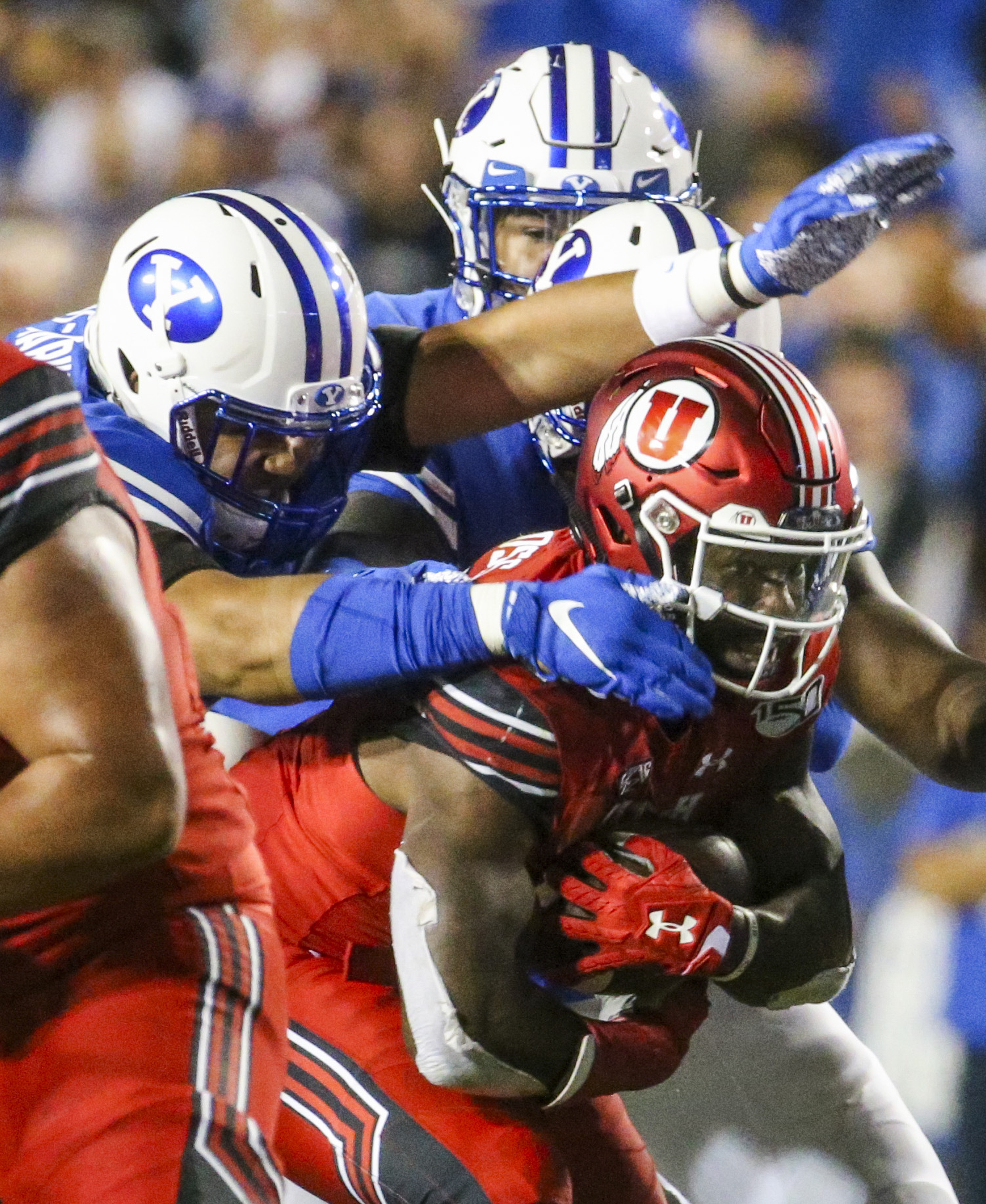 Utah running back Zack Moss battles his way through a group of BYU defenders during game at LaVell Edwards Stadium in Provo.