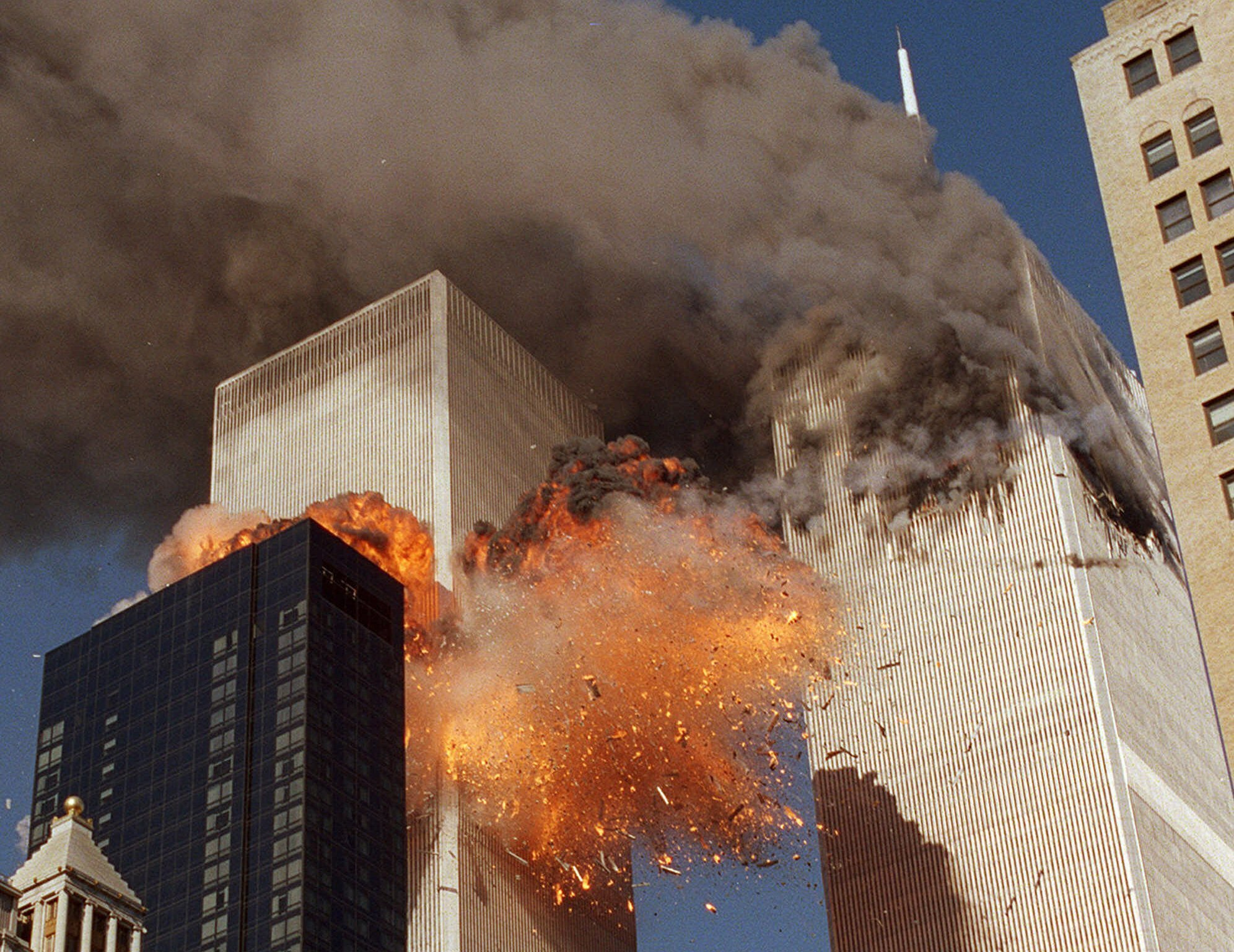 Smoke billows from one of the towers of the World Trade Center and flames and debris explode from the second tower on Sept. 11, 2001.