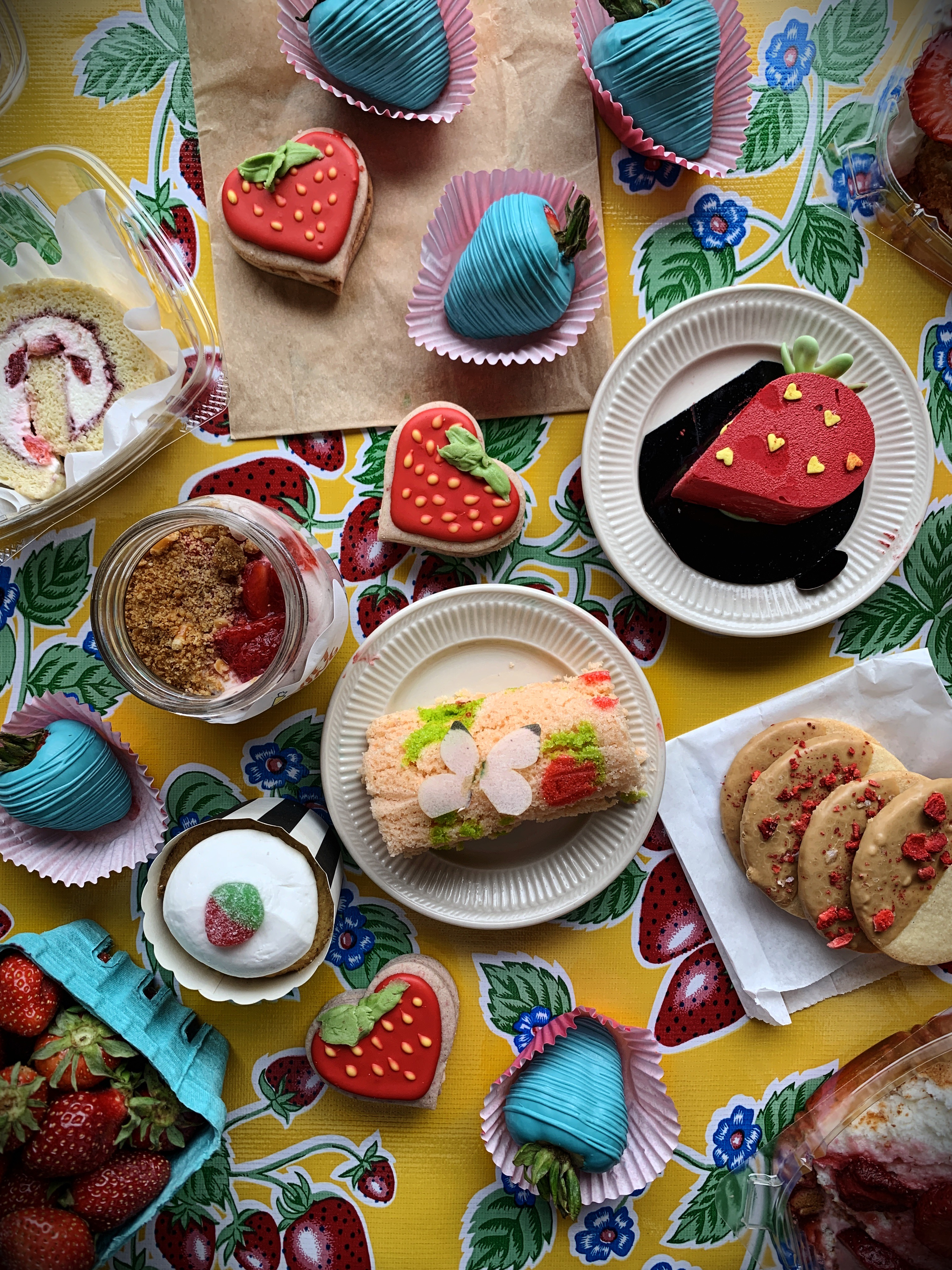 A strawberry cookie, roulade cake, and pastry sit on a table for the Portland Strawberry Museum.