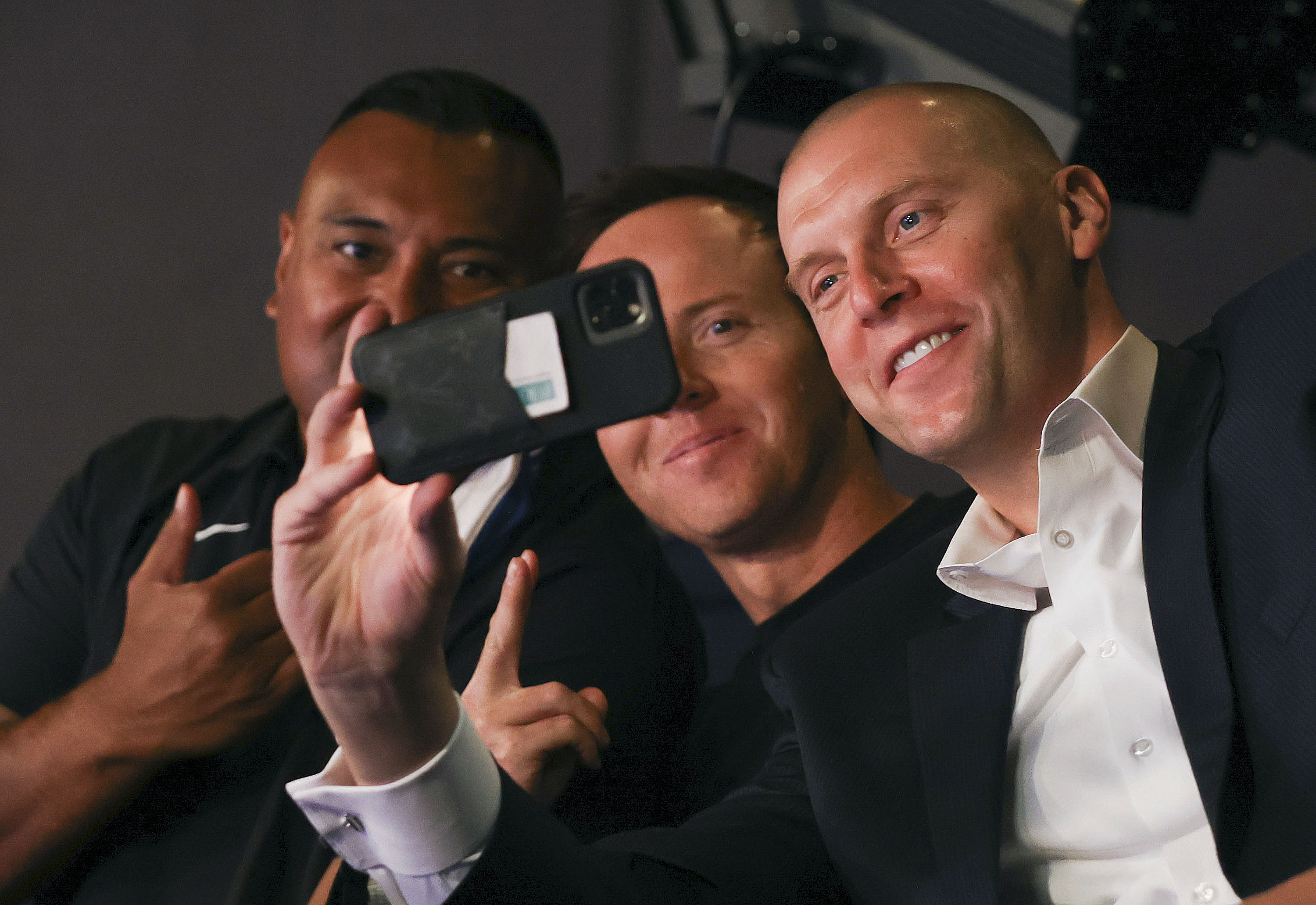 BYU football coach Kalani Sitake, Utah Jazz owner Ryan Smith, and BYU basketball coach Mark Pope take a selfie during a press conference announcing that BYU has accepted an invitation to the Big 12 Conference.
