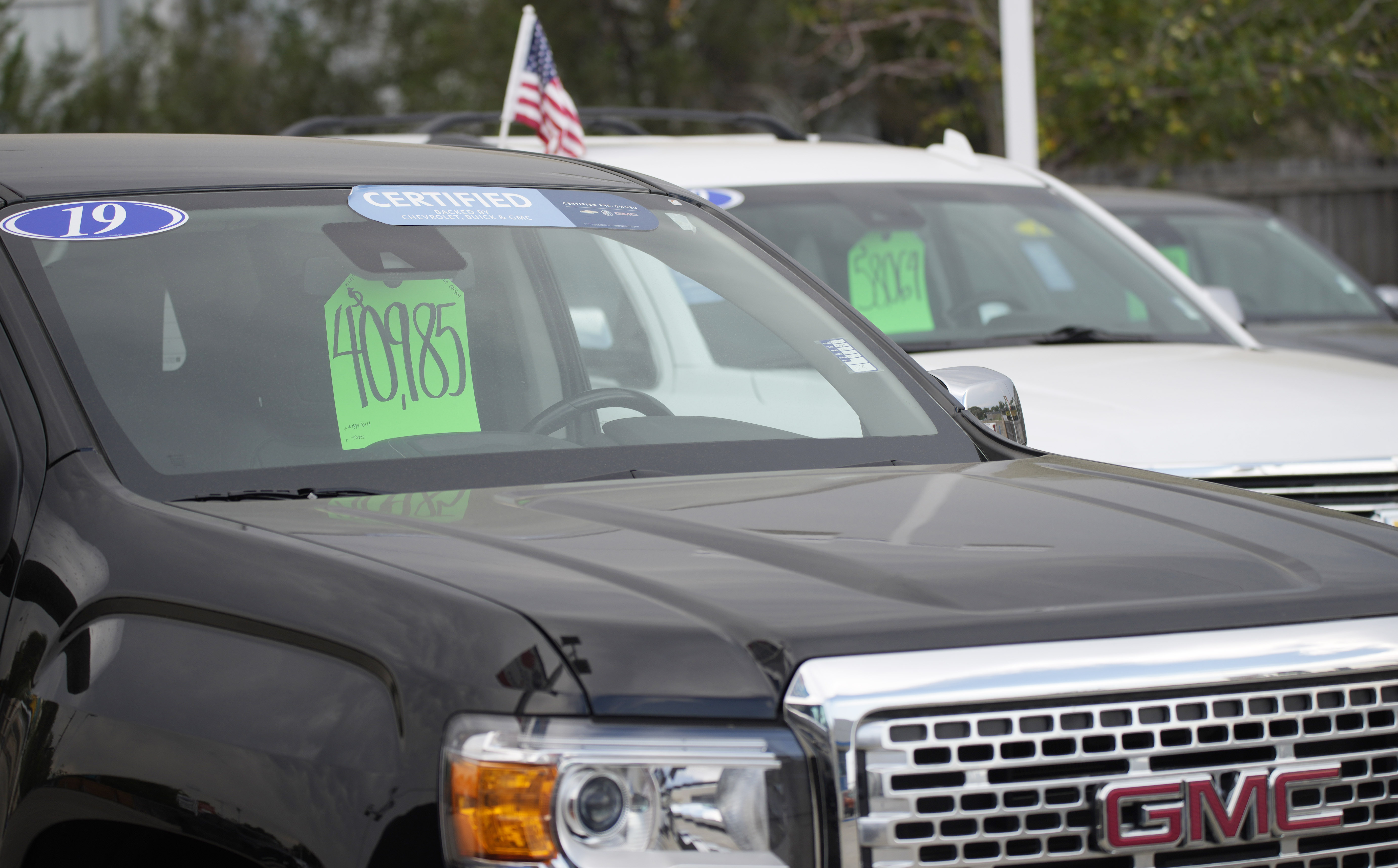 The price for a used 2019 GMC pickup truck is displayed in the windshield of the vehicle at Chevrolet dealership in Colorado.