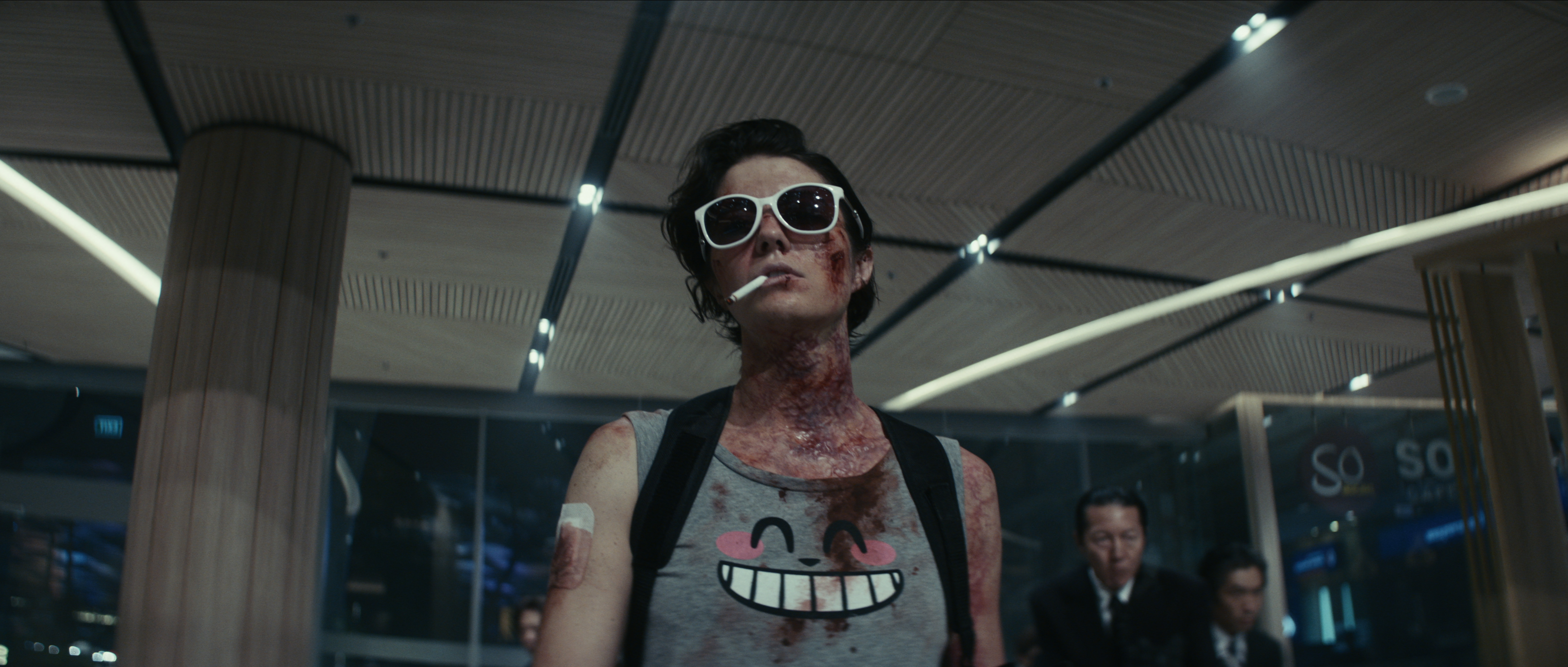 Mary Elizabeth Winstead, in sunglasses and a bloody Totoro shirt, in Netflix's Kate