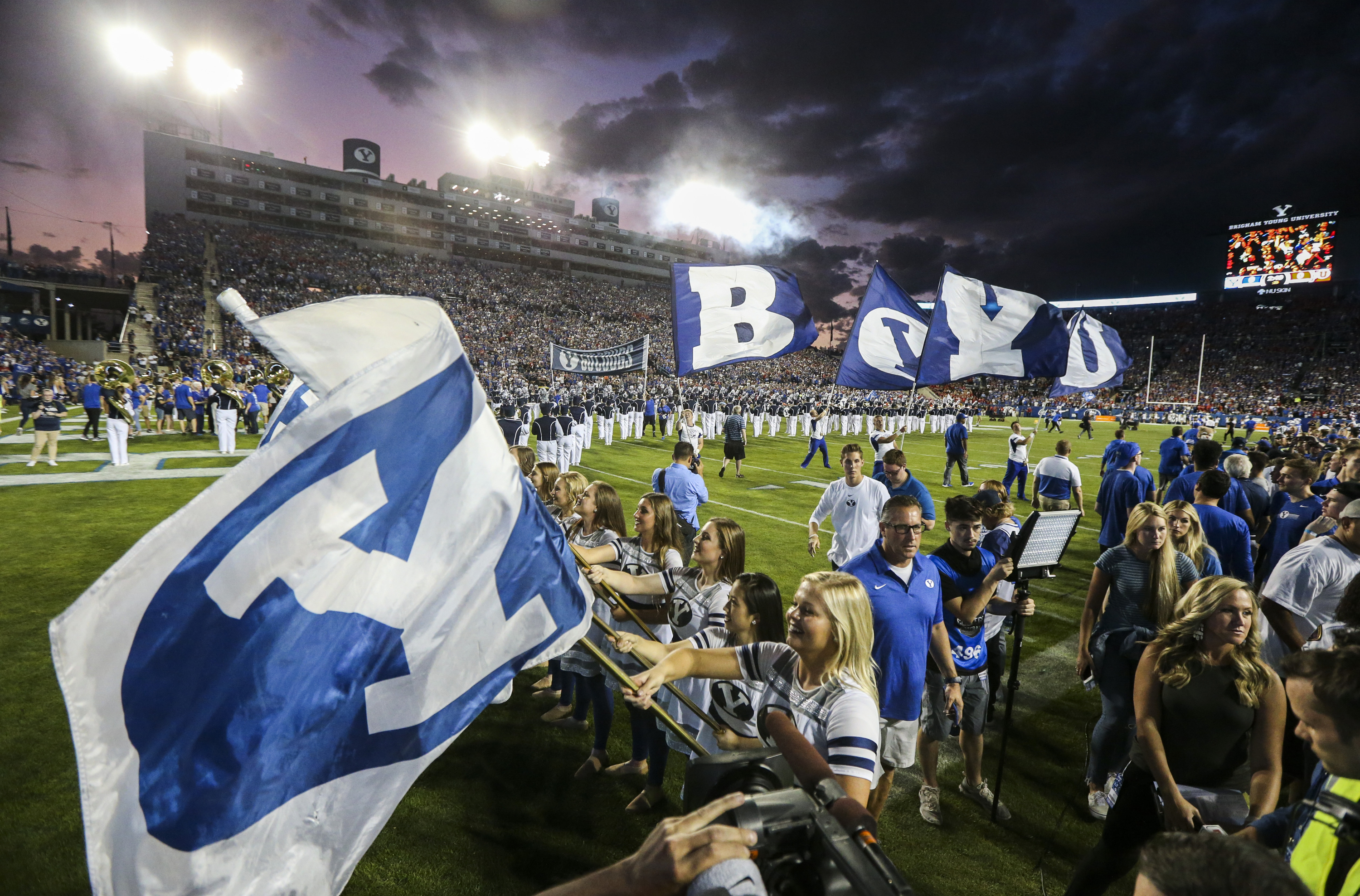 The BYU Spirit Squad waves their team flags after running out