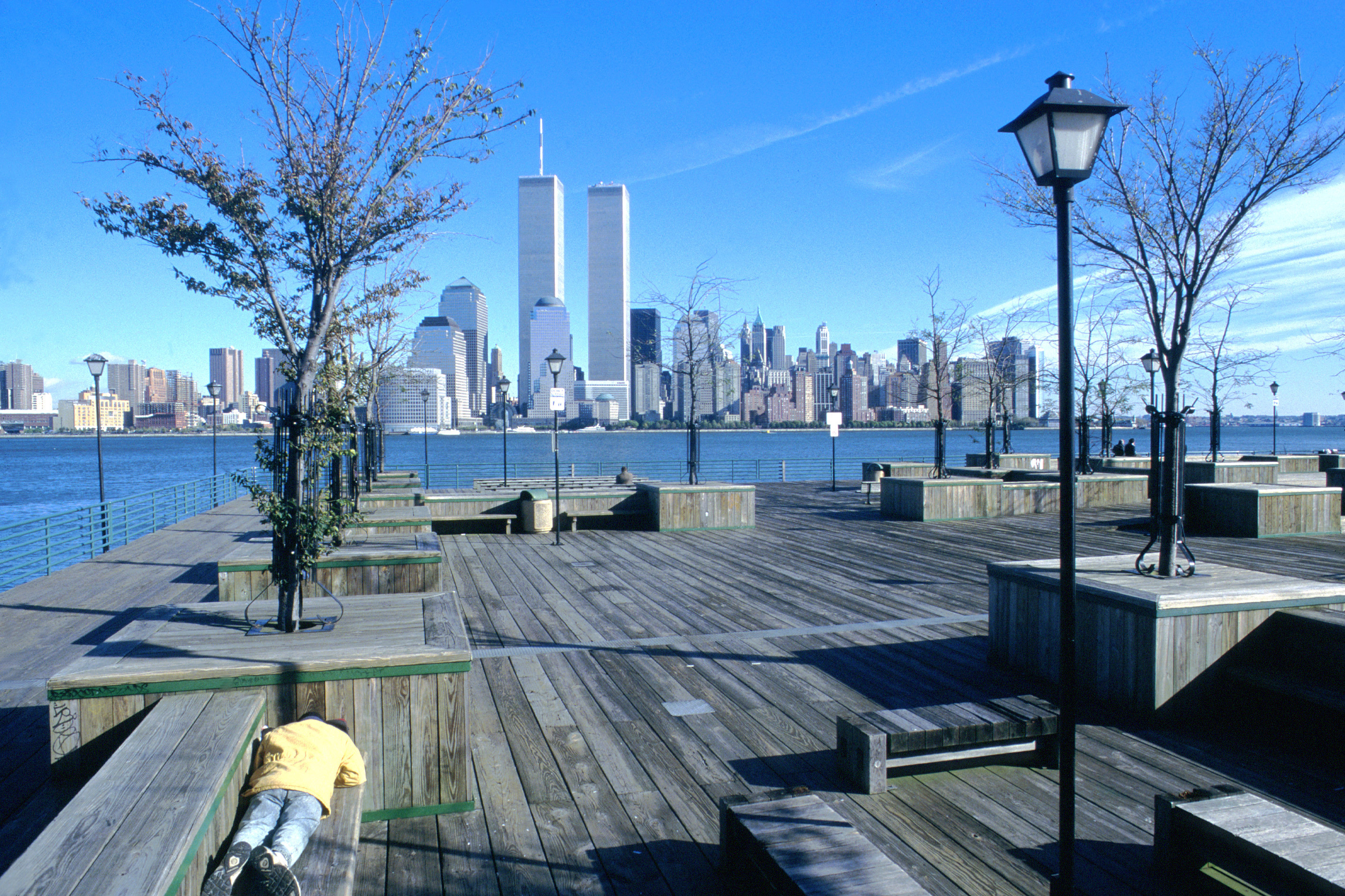 Person lying on bench on pier overlookin