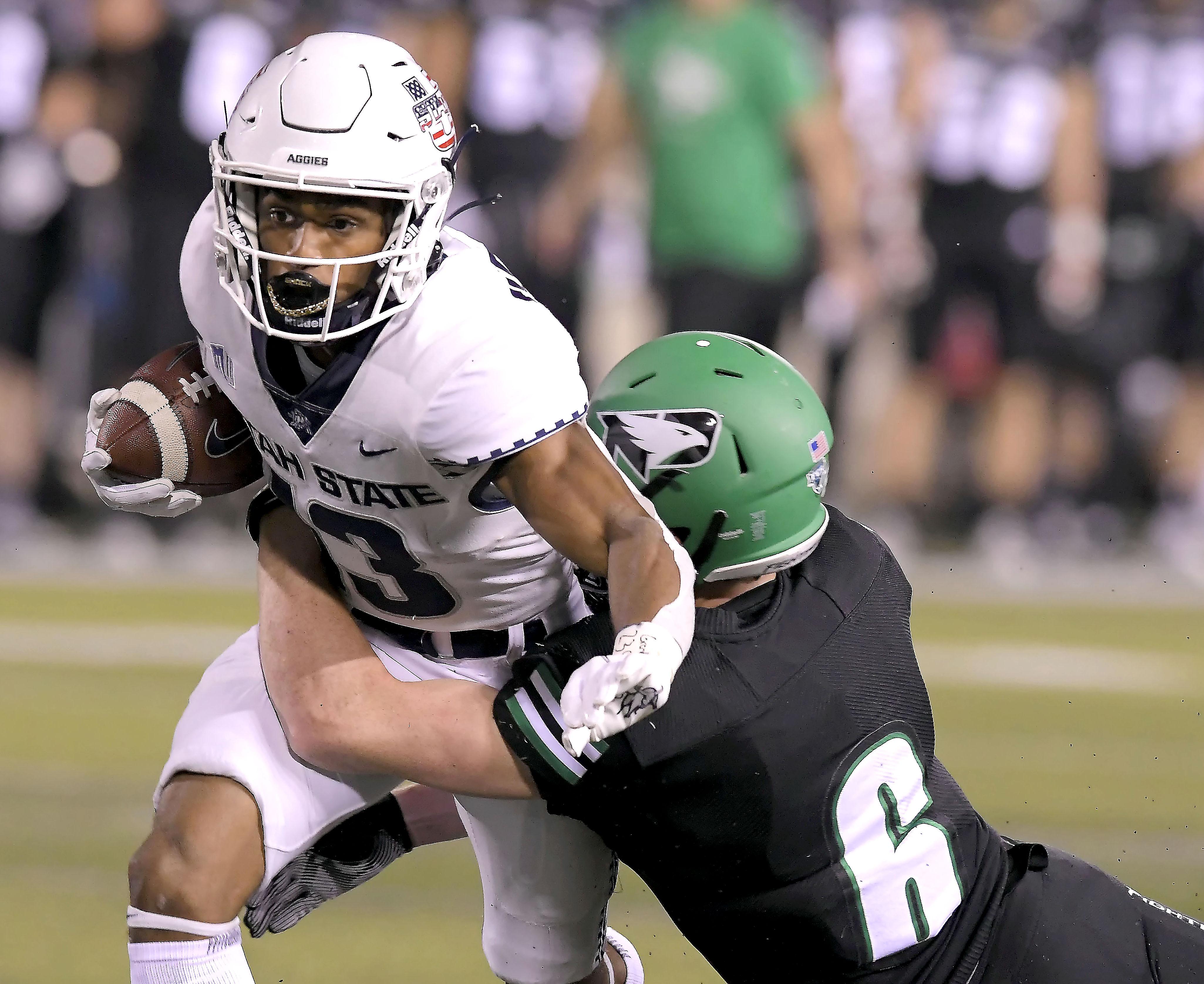 Utah State wide receiver Deven Thompkins is tackled by North Dakota defensive back Evan Holm.