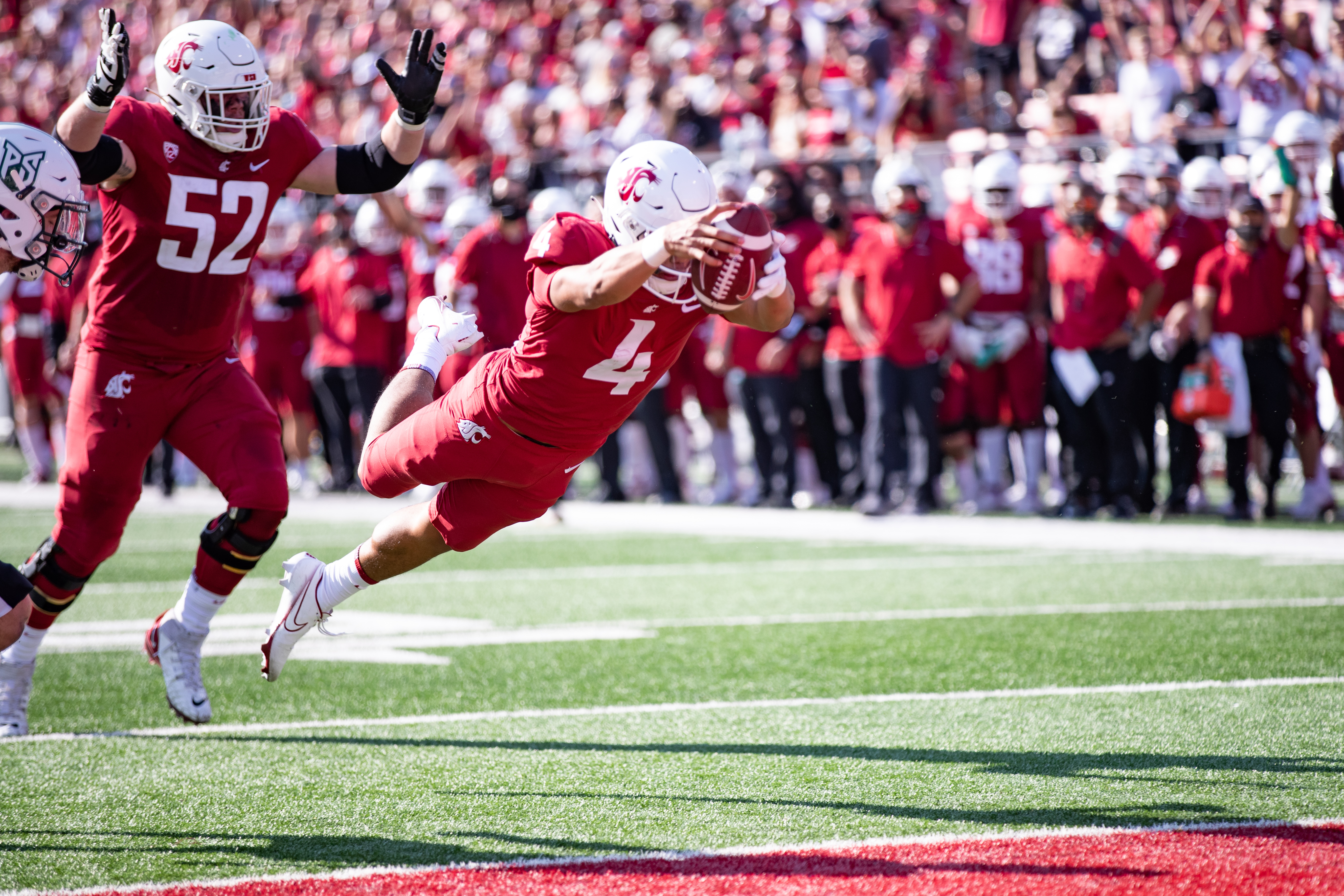 PULLMAN, WA - SEPTEMBER 11: Washington State quarterback Jayden de Laura (4) leaps into the end zone in the first half of a non-conference matchup between the Portland State Vikings and the Washington State Cougars on September 11, 2021, at Martin Stadium in Pullman, WA.