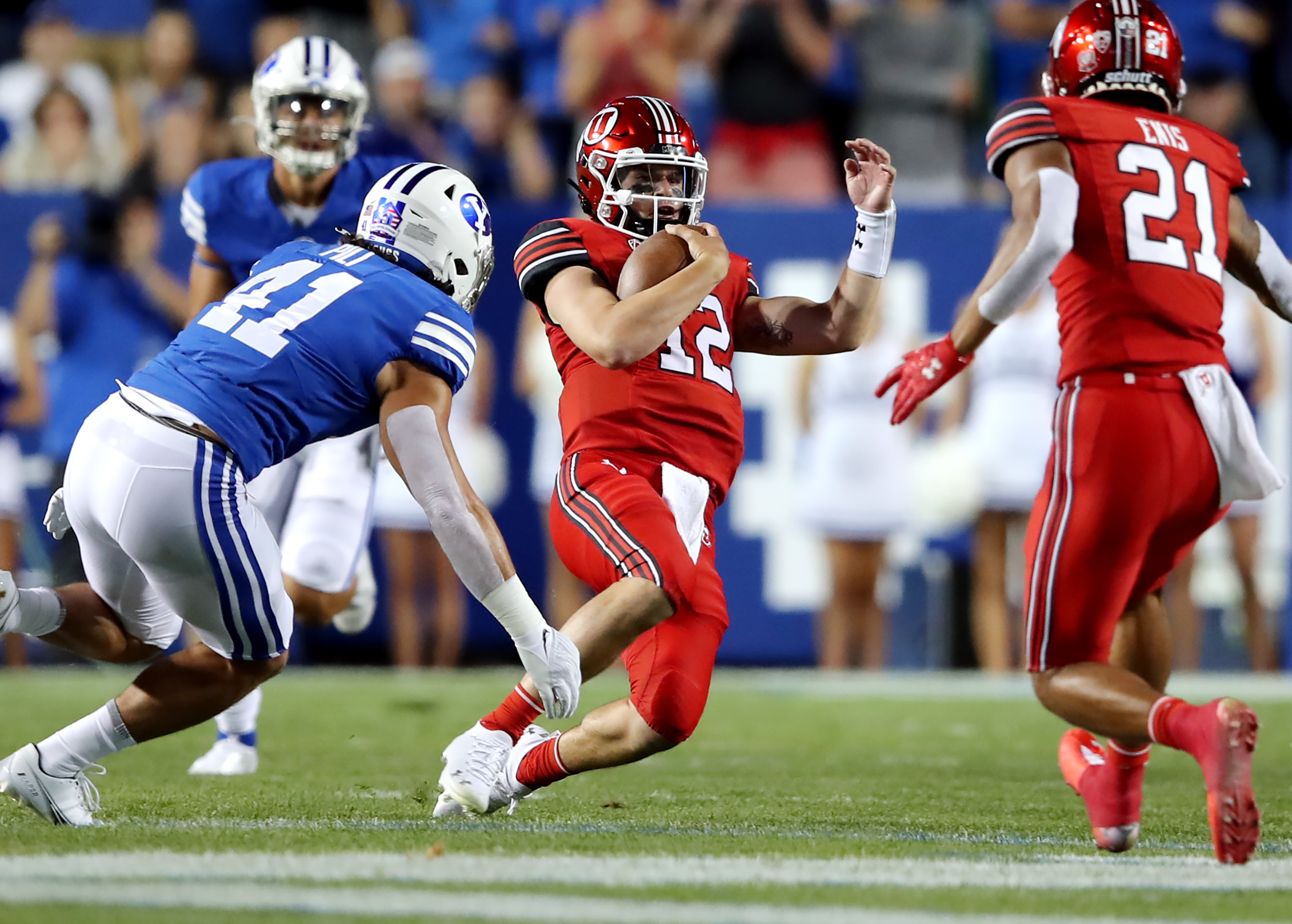Utah Utes quarterback Charlie Brewer, wearing a red helmet and red jersey, slides down with Brigham Young Cougars linebacker Keenan Pili, wearing a white helmet and royal blue jersey
