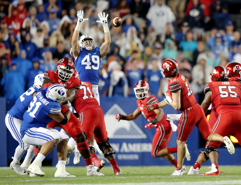 Brigham Young Cougars linebacker Payton Wilgar (49) knocks down a pass by Utah Utes quarterback Charlie Brewer (12) as BYU and Utah play.