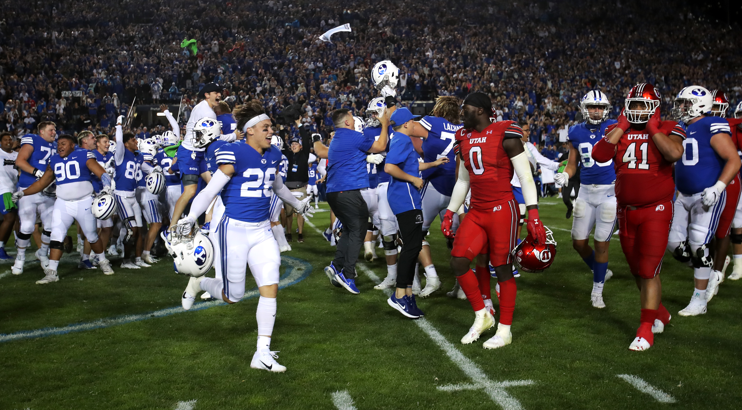 BYU players celebrate and Utah players look for the exit as the crowd rushes the field