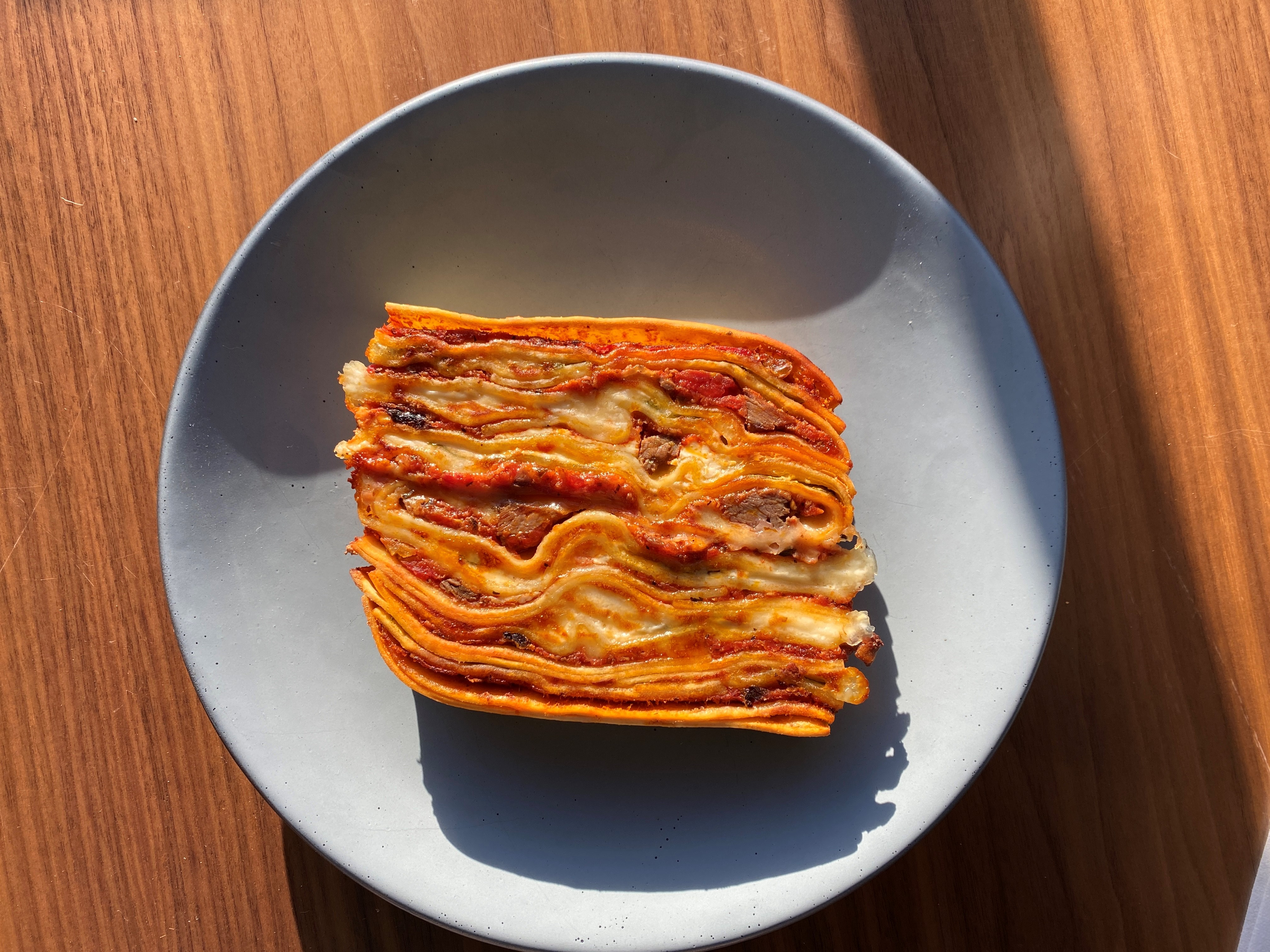 Overhead view of lasagna, positioned on its side so the many-layered cross-section is visible. It's on a pale gray plate on a wooden table.