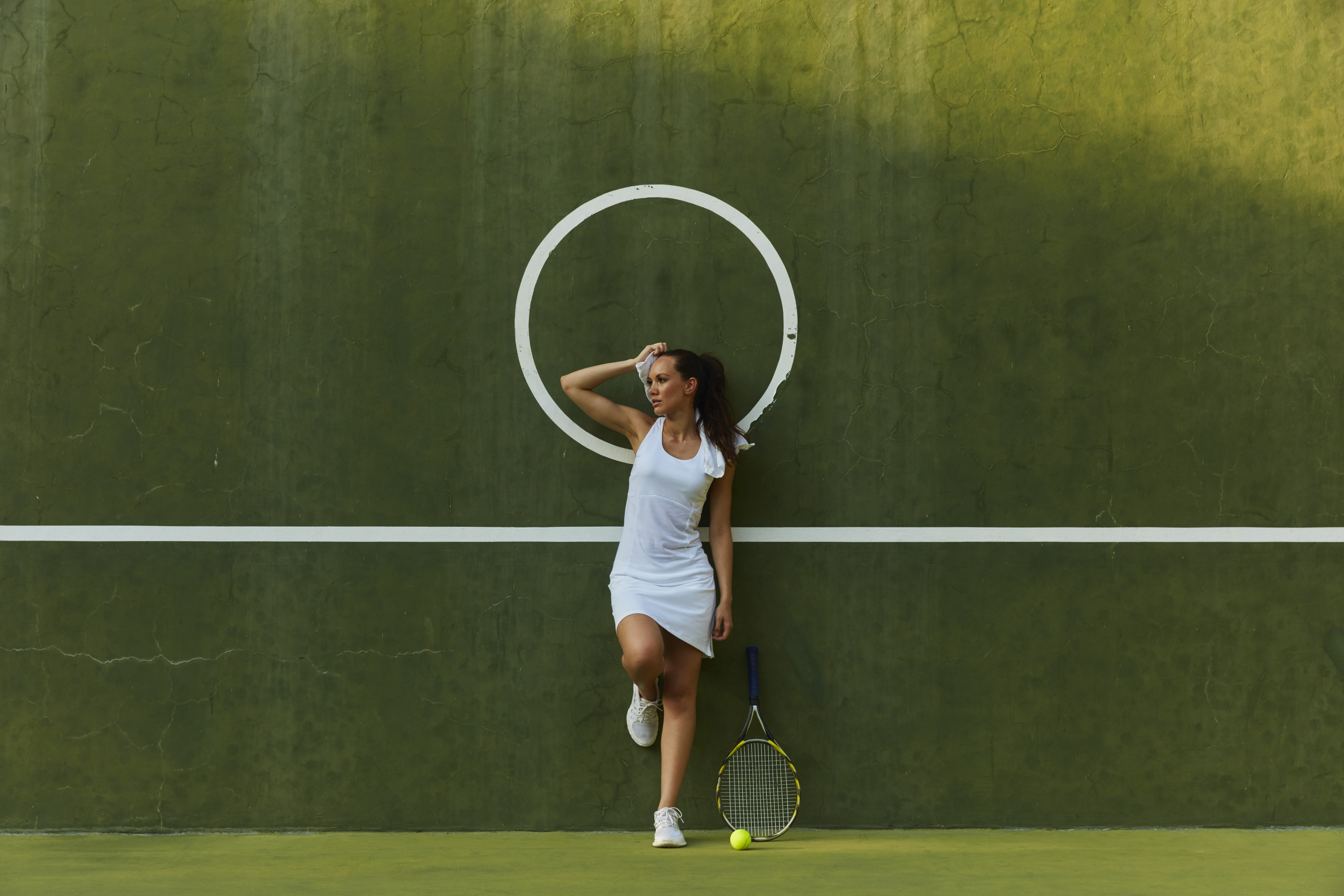 A woman poses in a white tennis dress, holding a tennis racket against a green wall.