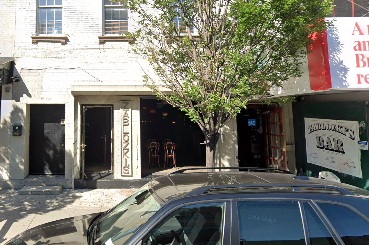 A streetside shot of a bar entrance with cars parked out front.