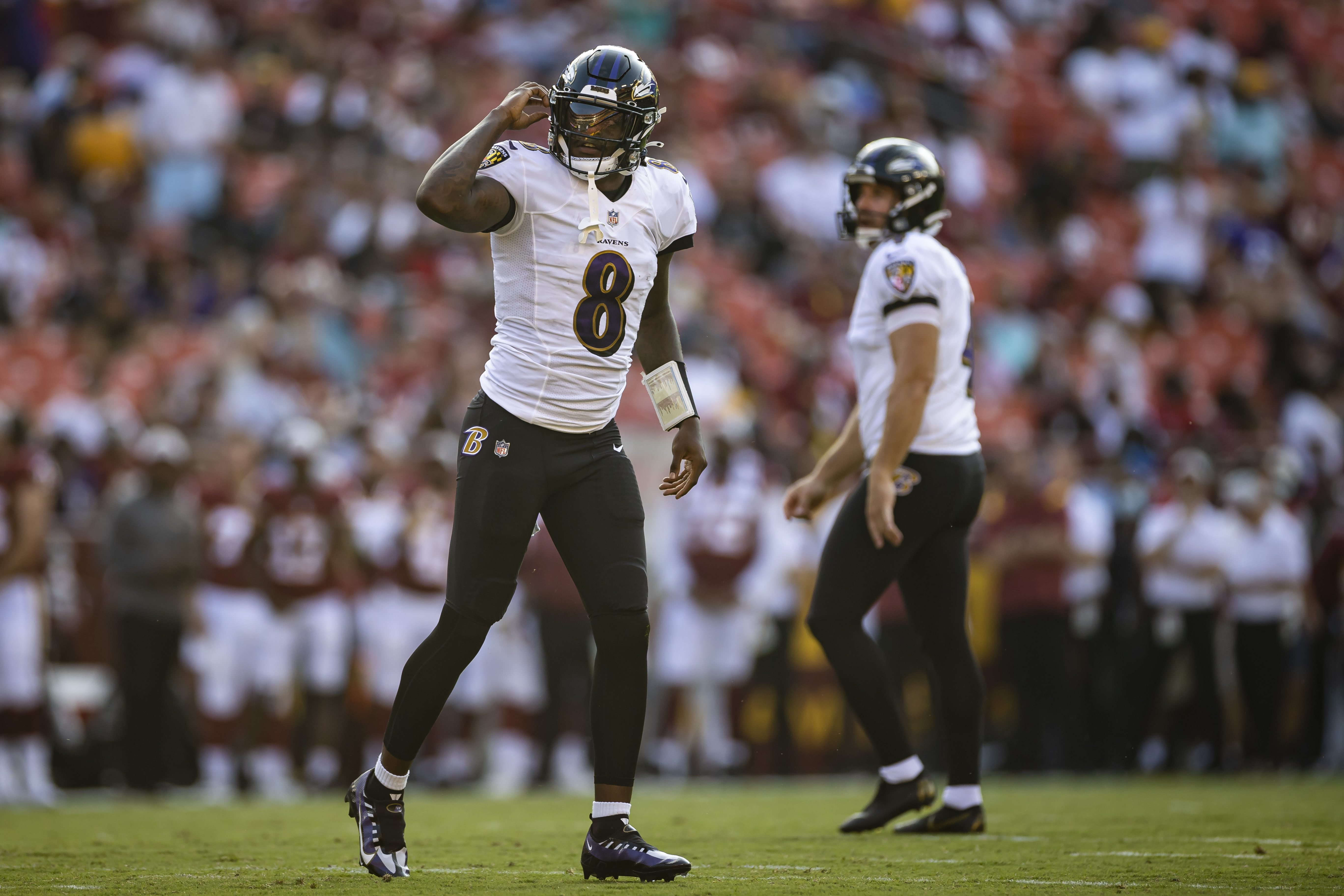 : Lamar Jackson #8 of the Baltimore Ravens looks on against the Washington Football Team during the first half of the preseason game at FedExField on August 28, 2021 in Landover, Maryland.