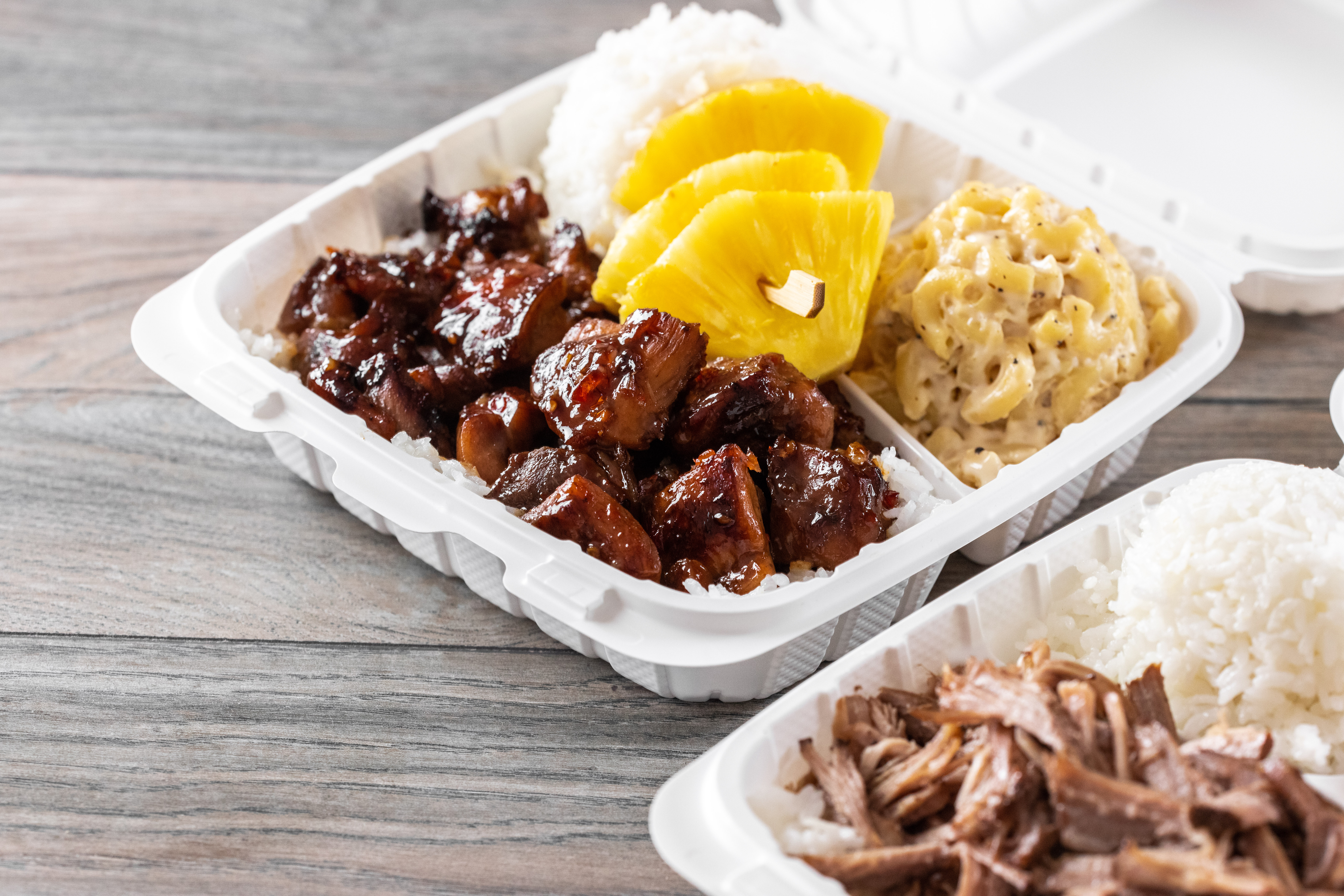 A takeout container filled with chicken coated in brown sauce, rice, macaroni salad and garnished with wedges of pineapple