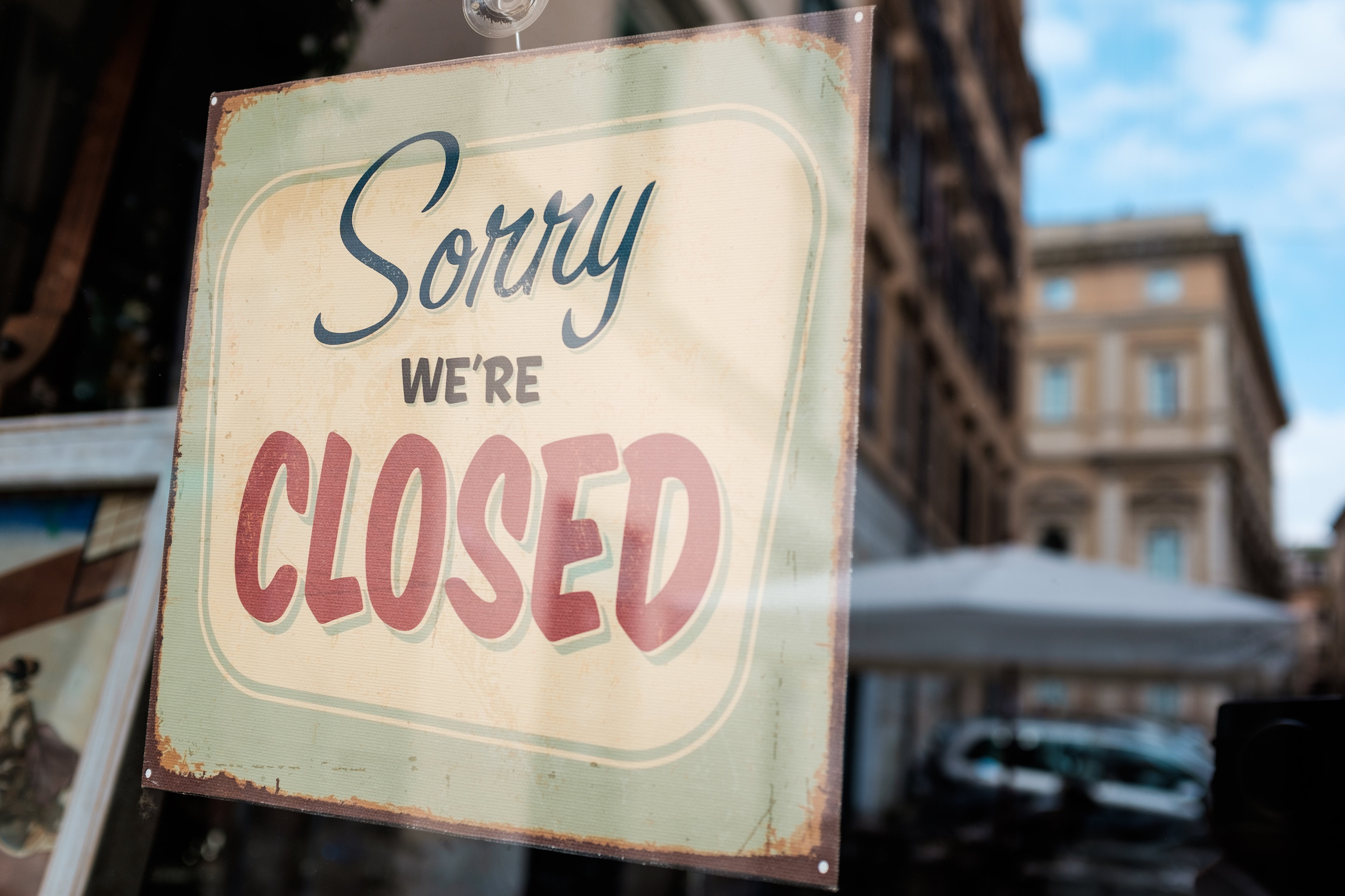 """A sign that reads """"Sorry, We're Closed"""" on a door"""