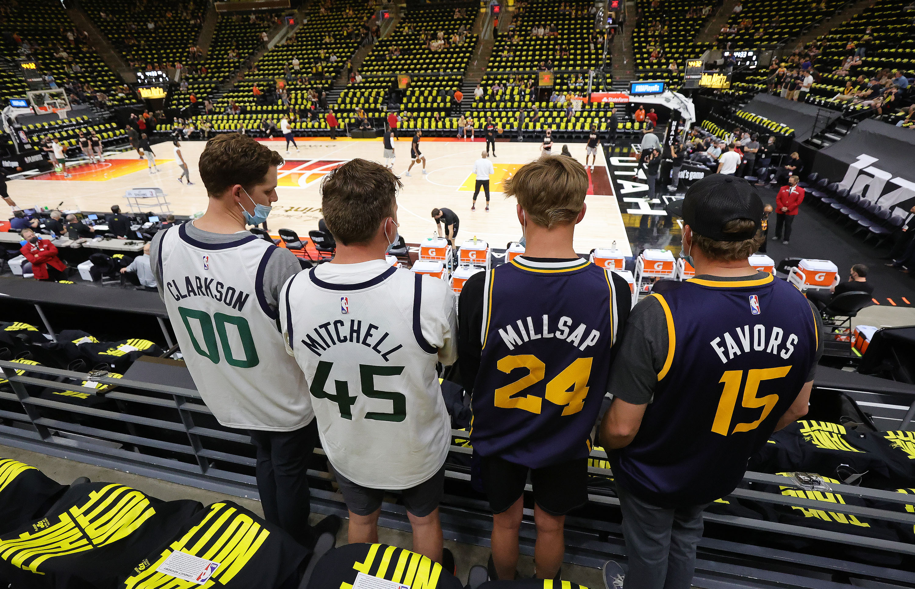 """Four Utah Jazz fans wearing """"Clarkson,"""" """"Mitchell,"""" """"Millsap"""" and """"Favors"""" jerseys watch pregame activities for Game 5 of the NBA playoffs between the Utah Jazz and the LA Clippers in Salt Lake City on Wednesday, June 16, 2021."""