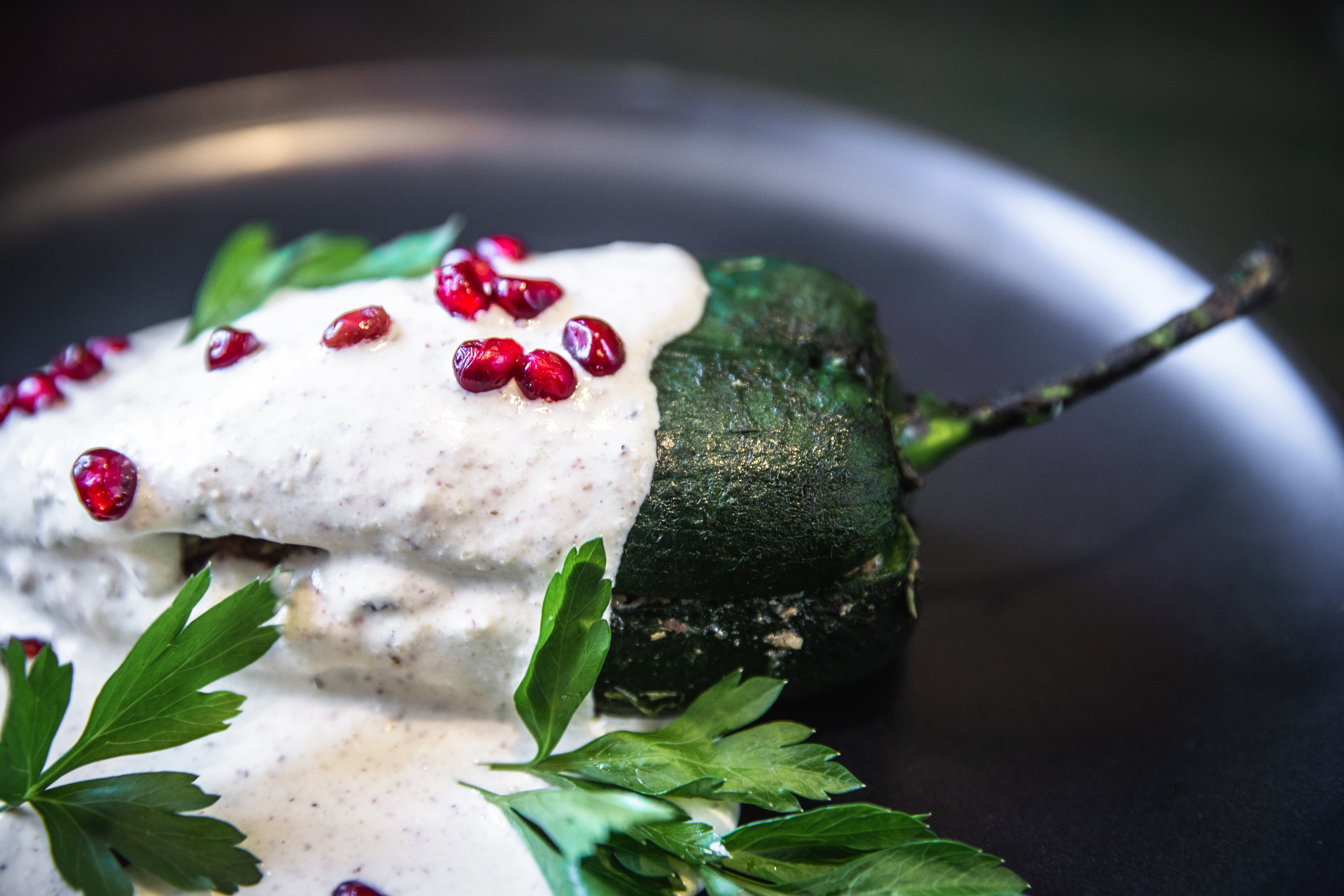 A green chile with cream and pomegranate on a black dish.