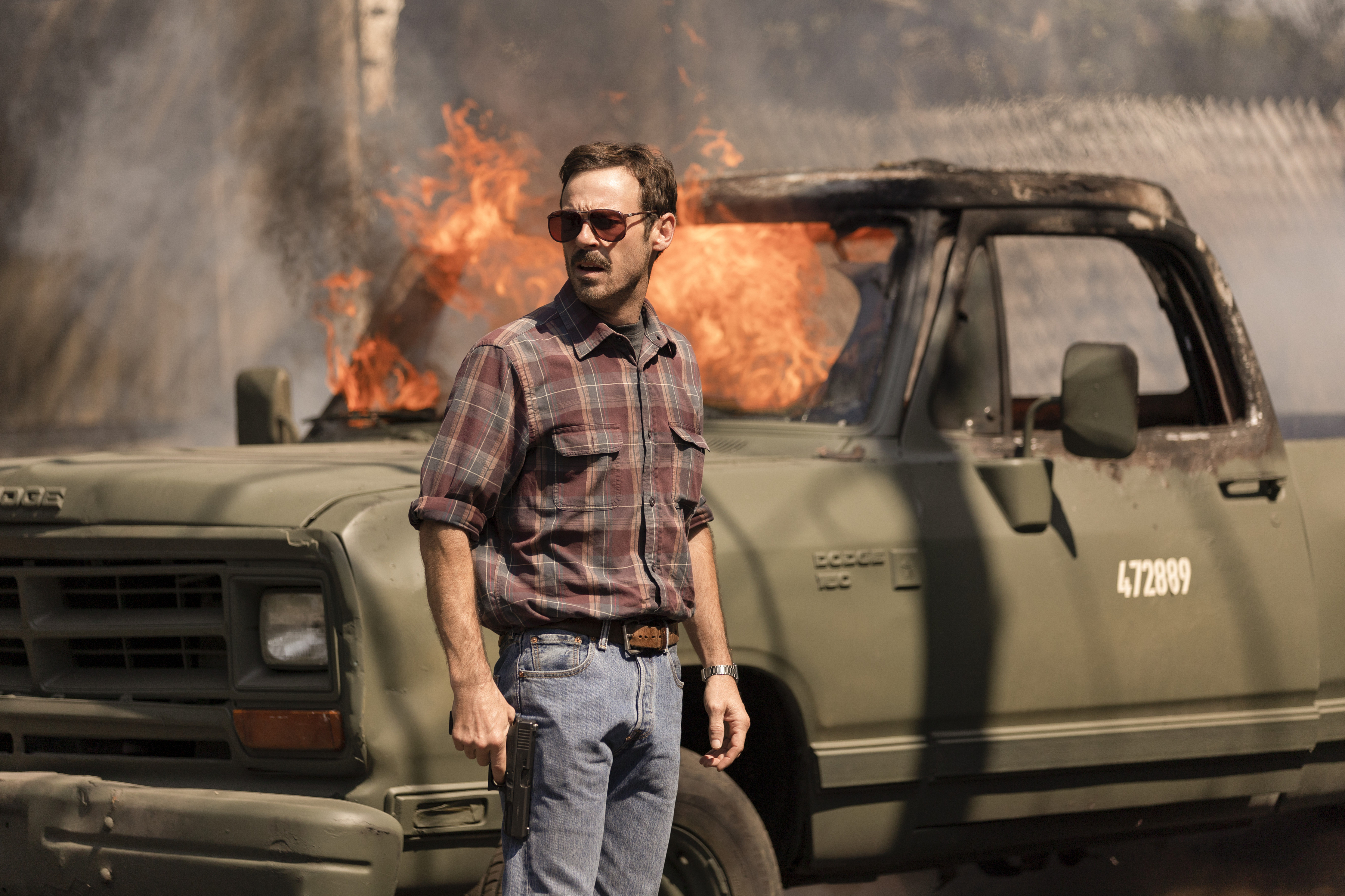 A man stands in front of a truck that's on fire in Narcos: Mexico season 3