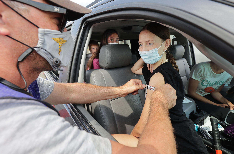 Utah Air National Guard Cpt. Raymond Searles gives Brynn Jackson a COVID-19 vaccine.