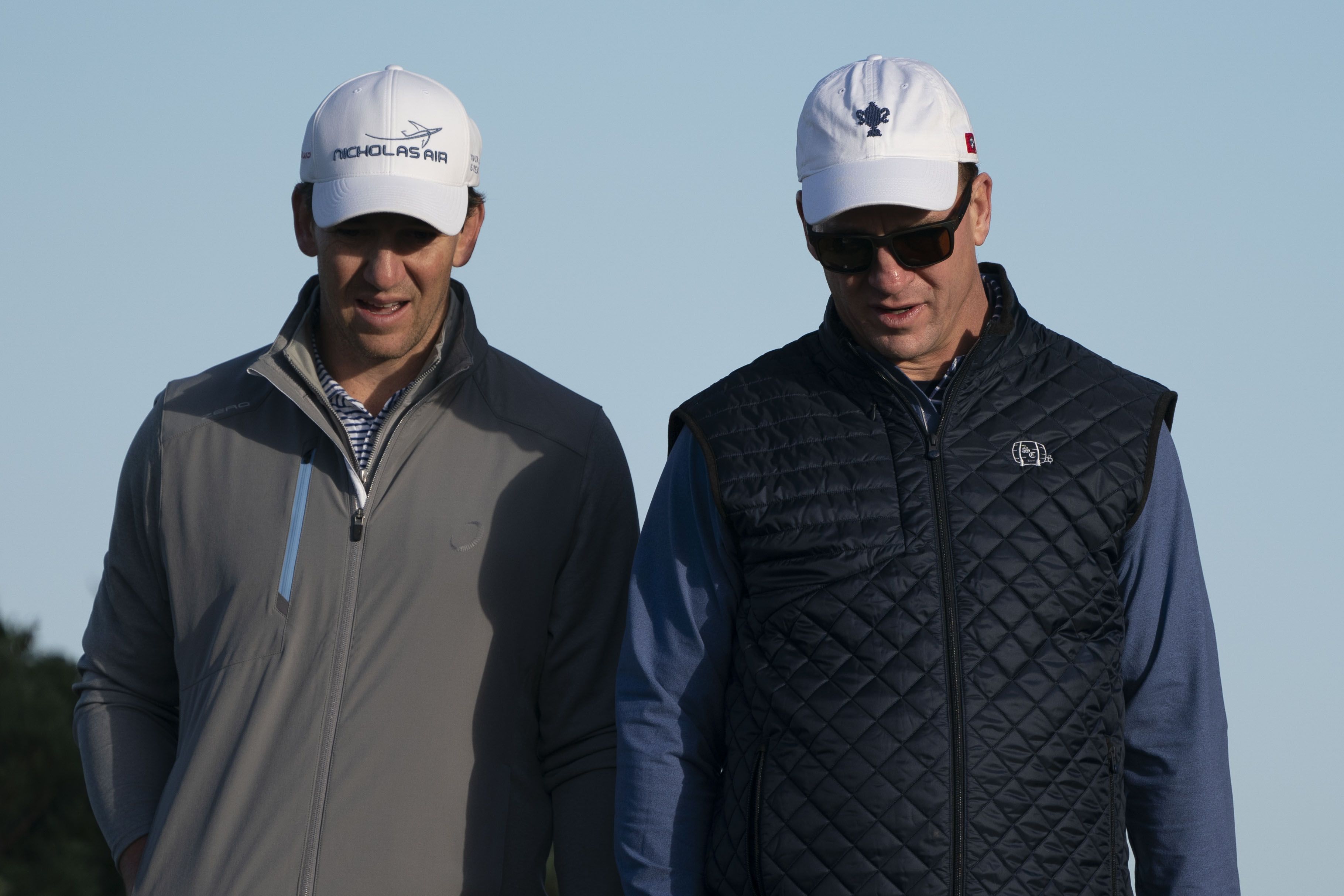 Eli Manning (left) and Peyton Manning (right) walk on the 11th hole during the second round of the AT&T Pebble Beach Pro-Am golf tournament at Monterey Peninsula Country Club - Shore Course.