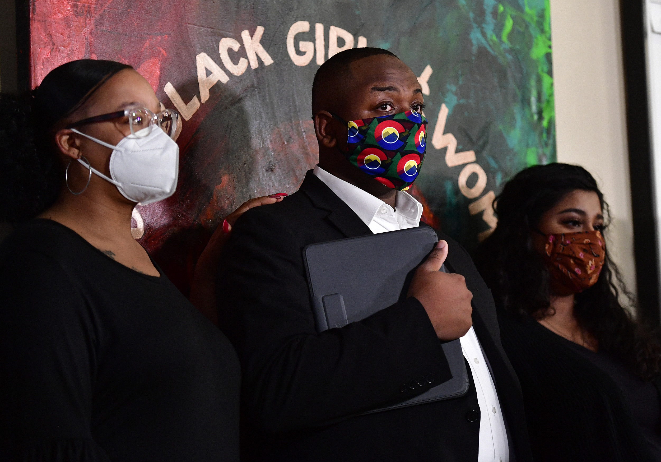 """Tay Anderson, wearing a face mask, stands with two women, one on either side of him. A painting on the wall behind him reads """"Black Girls and Women."""""""