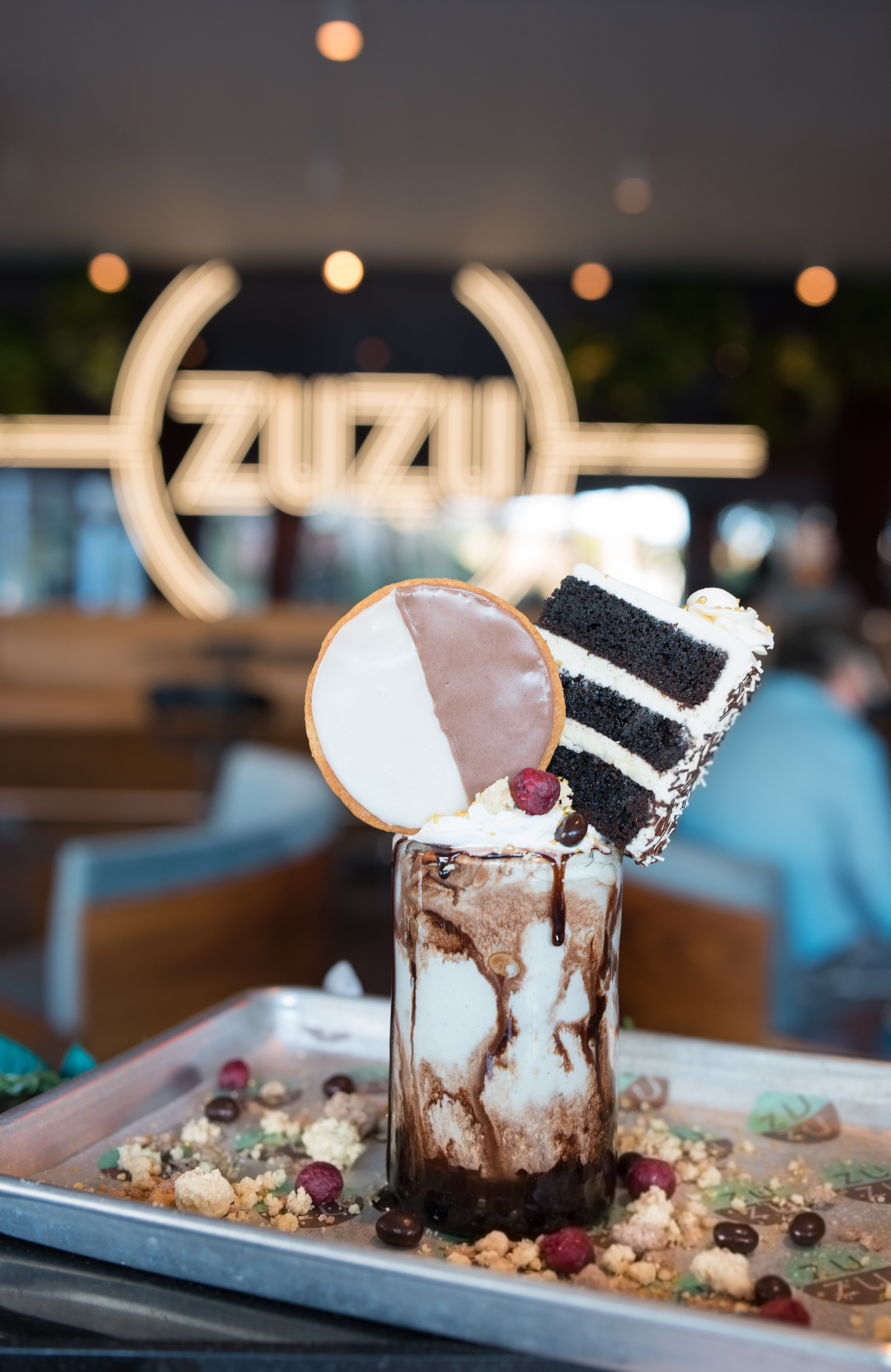 An over-the-top milkshake with a slice of chocolate cake with vanilla icing, a black and white cookie, and whipped cream with a cherry on top.