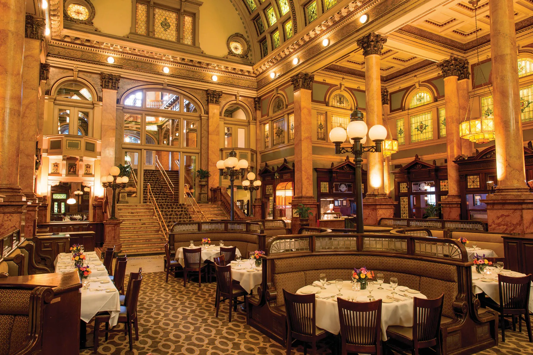 An opulent dining room with huge booths, long staircase, vaulted ceilings, old-style lamp posts, and stained glass