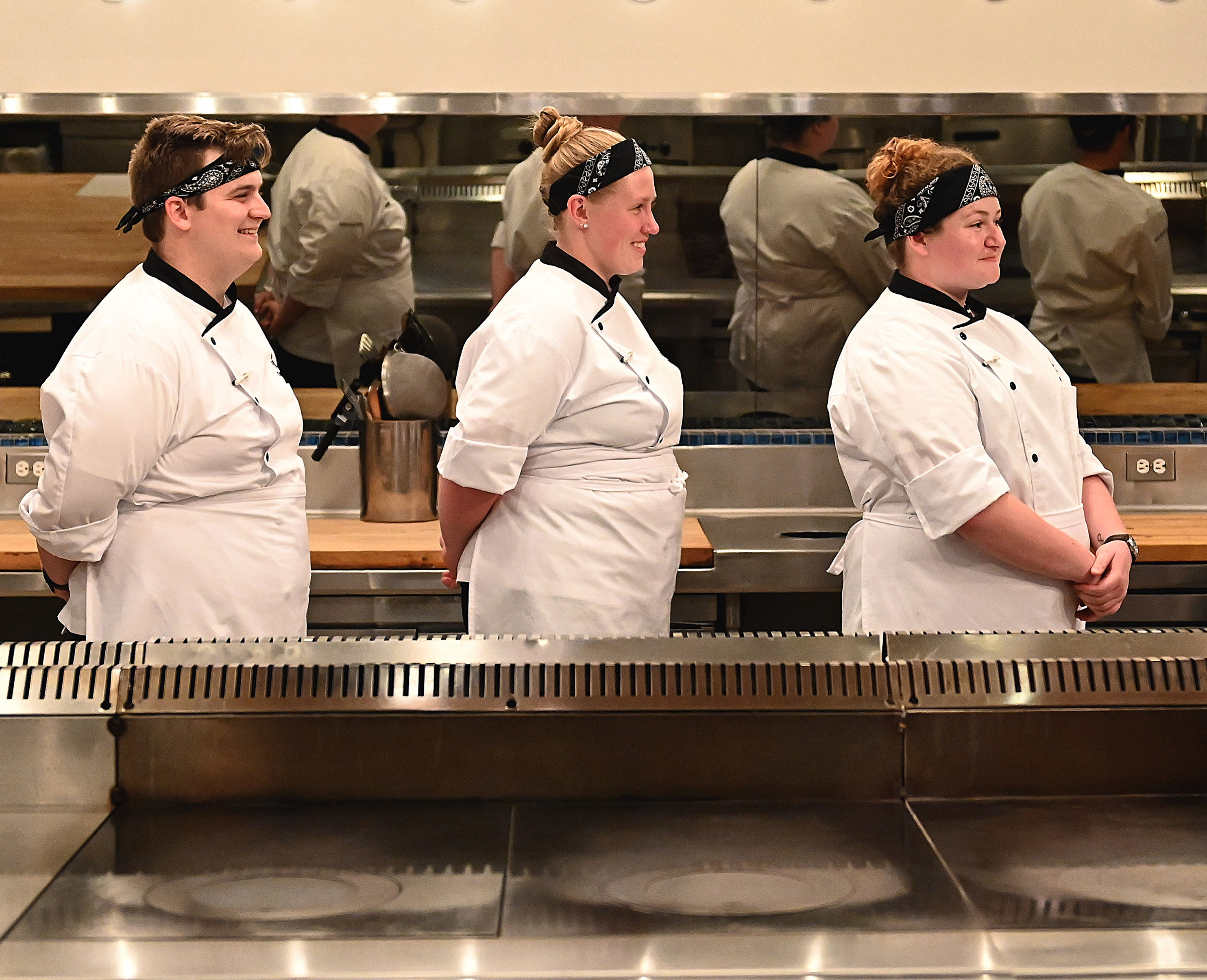 Three chefs, a man and two women, in white jackets face right.