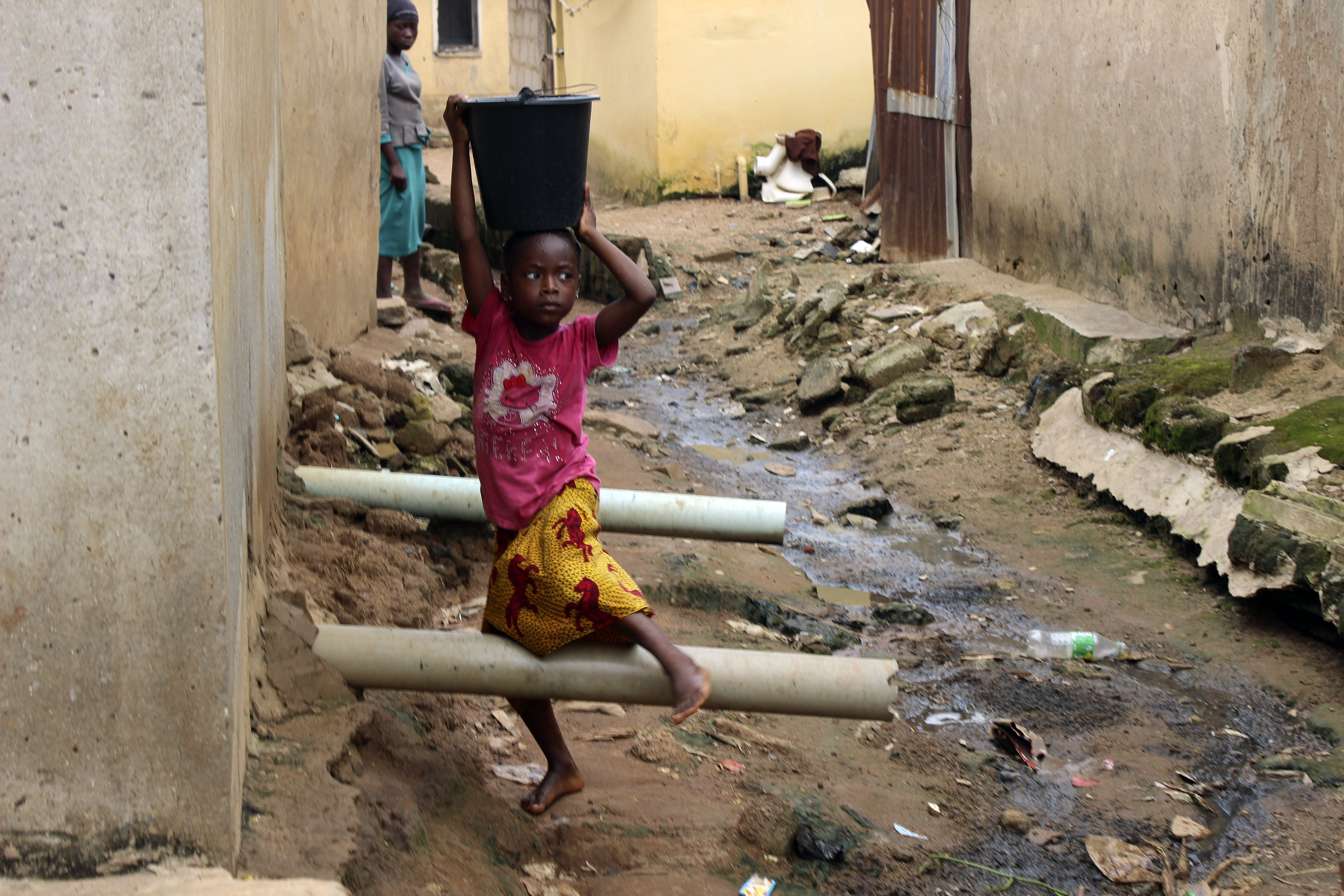 A girl carrying water on her head walks past sewage around houses in Abuja, Nigeria. The country is facing one of its worst cholera outbreaks in years, with more than 2,300 people dead from suspected cases as the West African nation struggles to deal with multiple disease outbreaks.