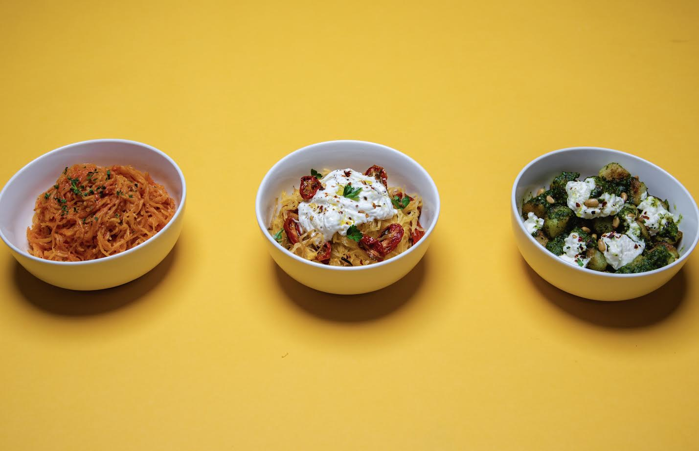 A yellow table shows off a trio of fake noodles in white bowls with sauce.