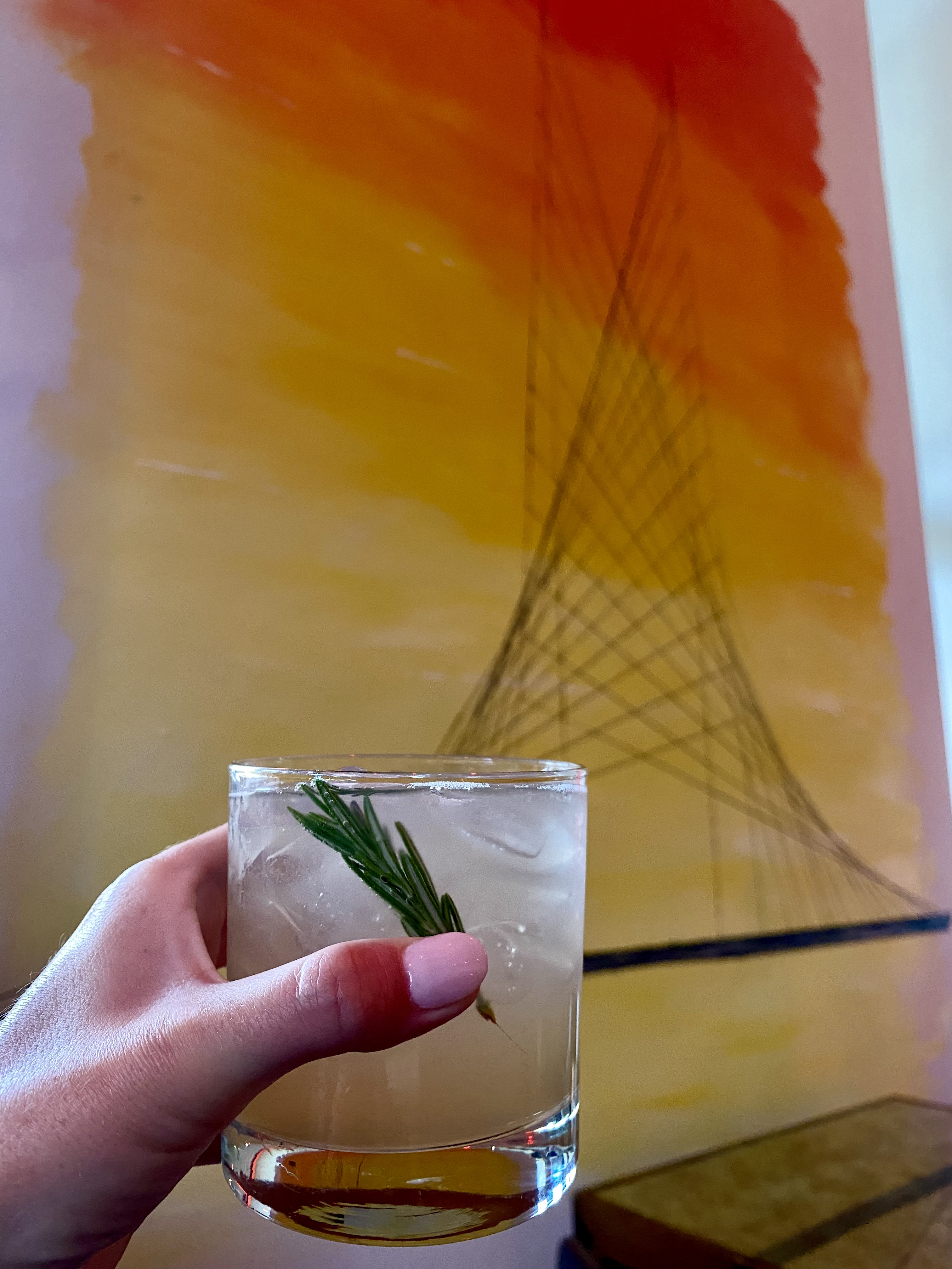 a manicured hand holding a rosemary gimlet cocktail in front of an orange and yellow modernist painting