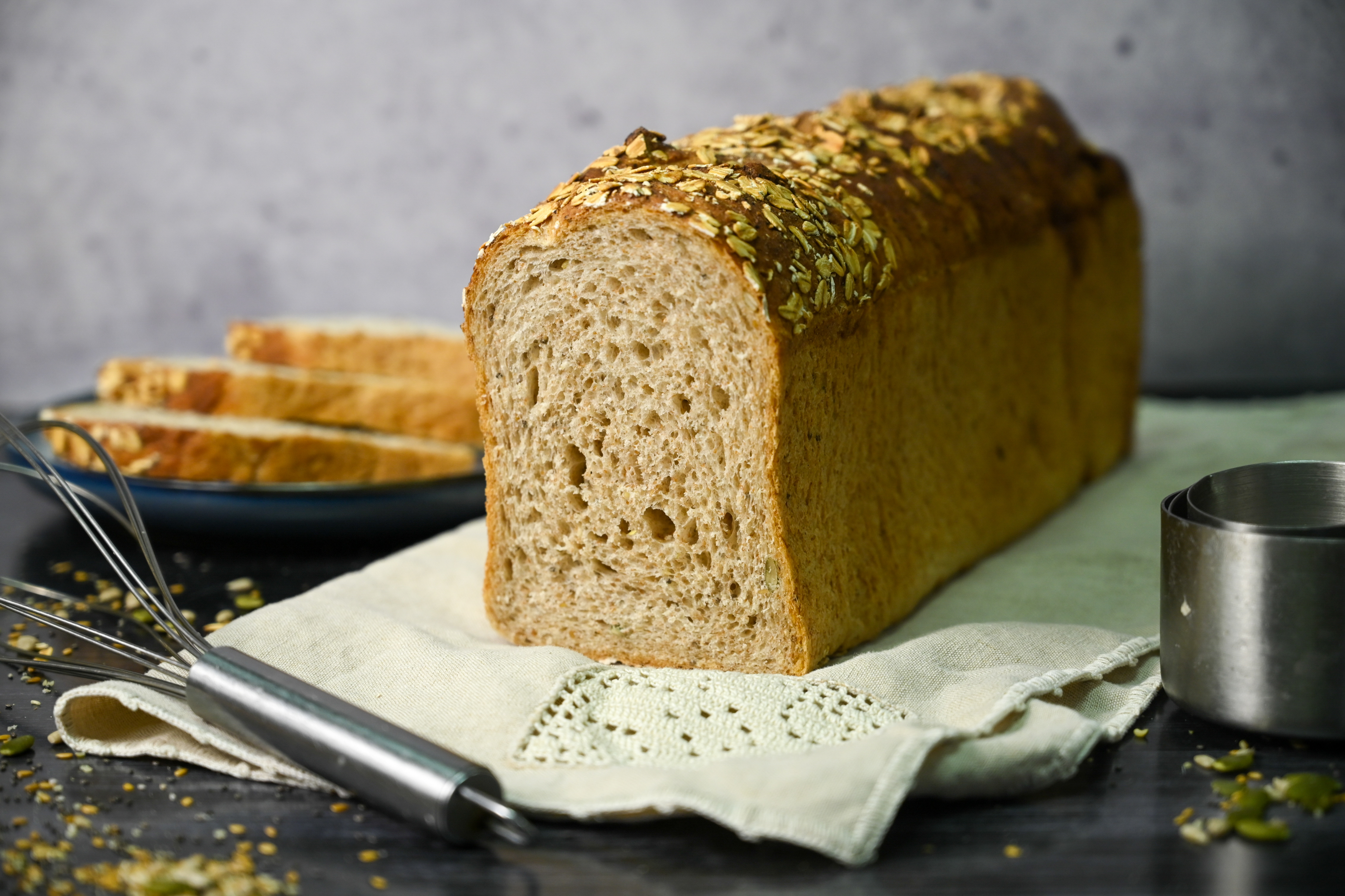 A tall, medium-brown loaf of bread is sliced near the end, with a stack of three slices piled up in the background. The loaf sits on an off-white cloth on a dark surface, with a metal whisk visible in the foreground.