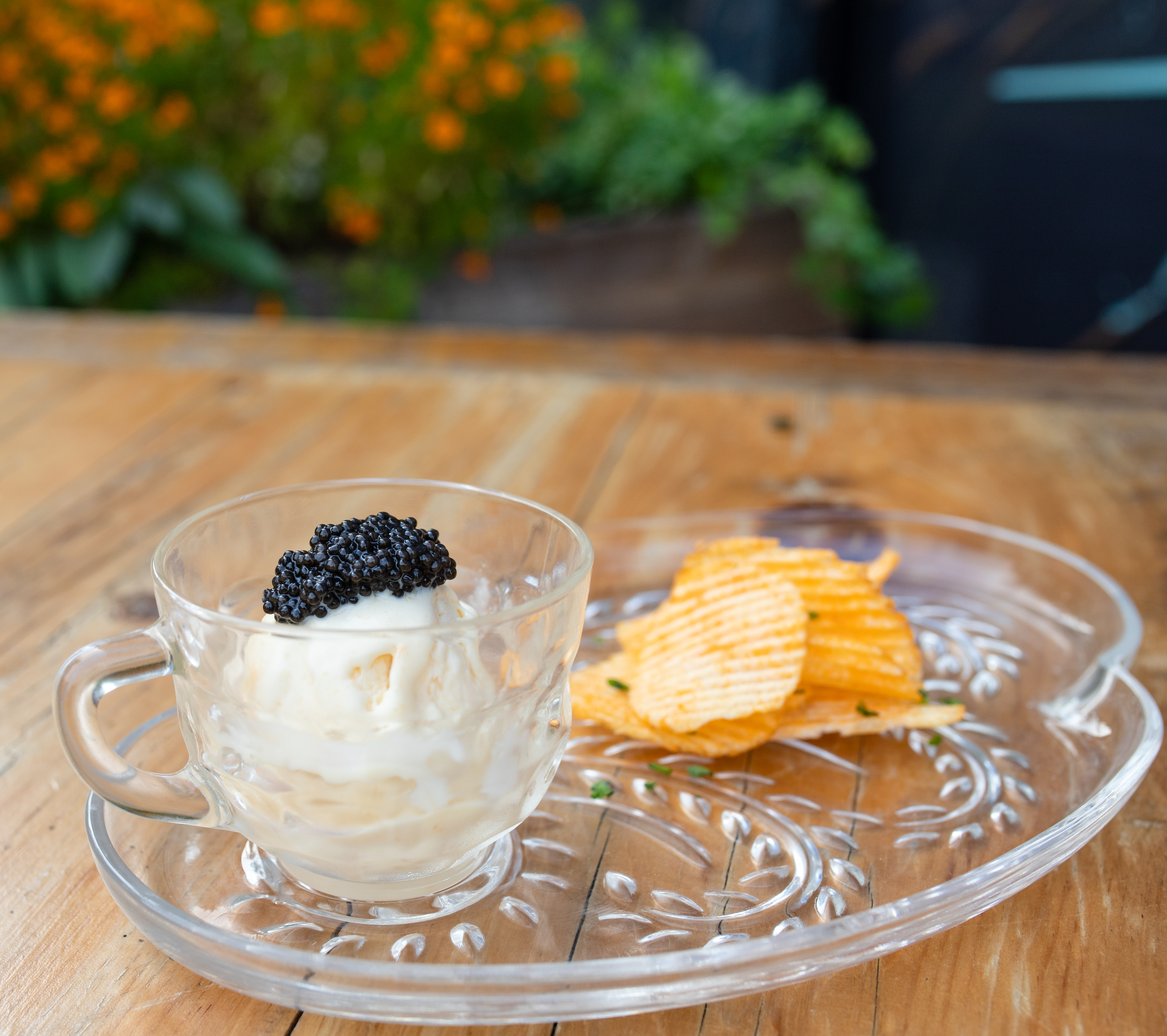 A small glass teacup holds a scoop of white ice cream with a dollop of black caviar on top. A small pile of orange potato chips sits beside it.