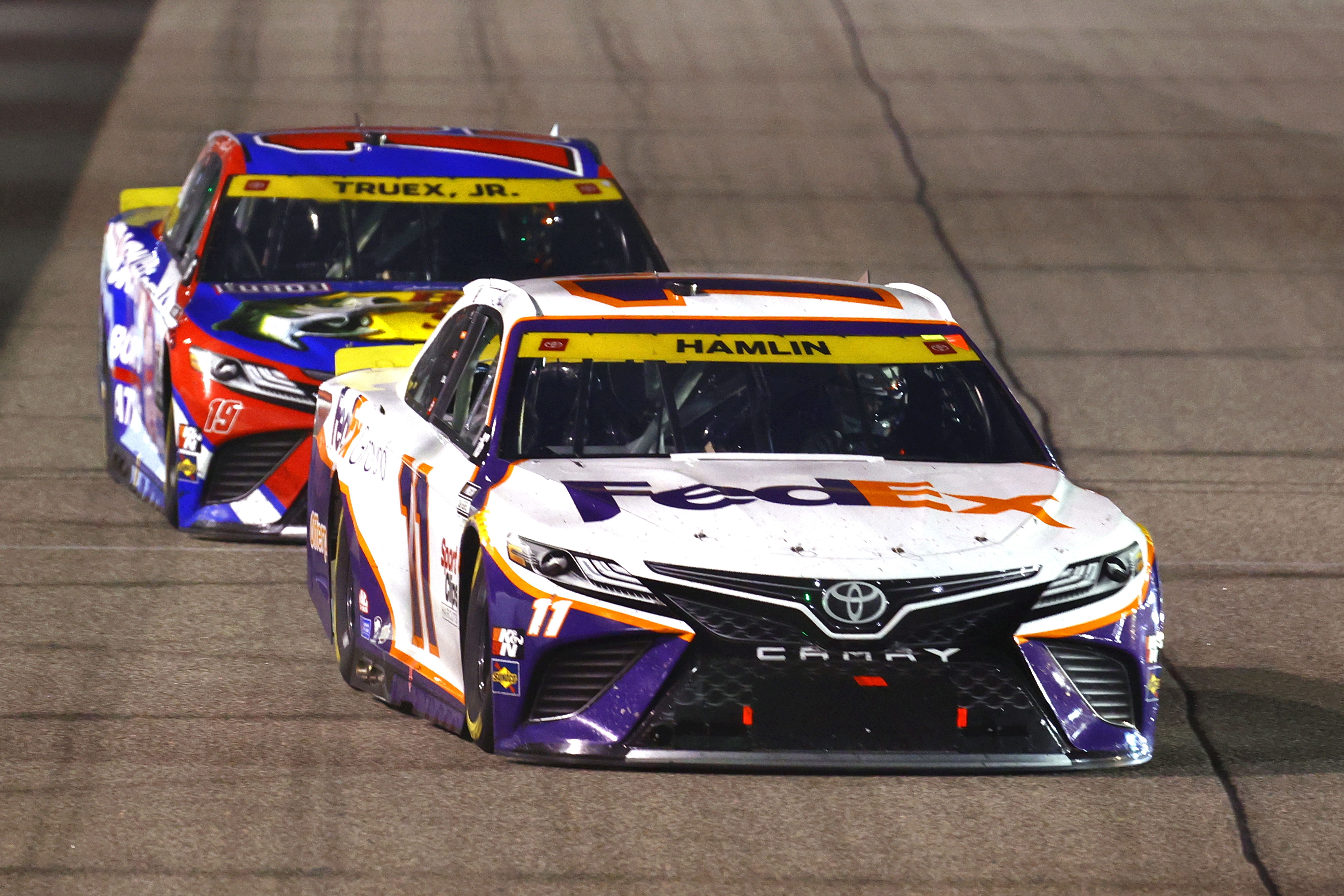 Denny Hamlin, driver of the #11 FedEx Ground Toyota, and Martin Truex Jr., driver of the #19 Bass Pro Shops Red White Blue Toyota, race during the NASCAR Cup Series Federated Auto Parts 400 Salute to First Responders at Richmond Raceway on September 11, 2021 in Richmond, Virginia.