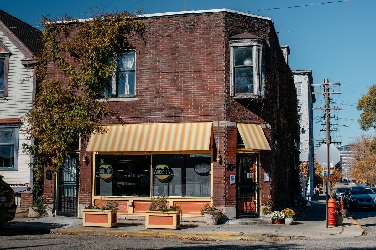 The exterior of the brick, vine-covered building where Mudgie's is located has orange and white striped awnings.