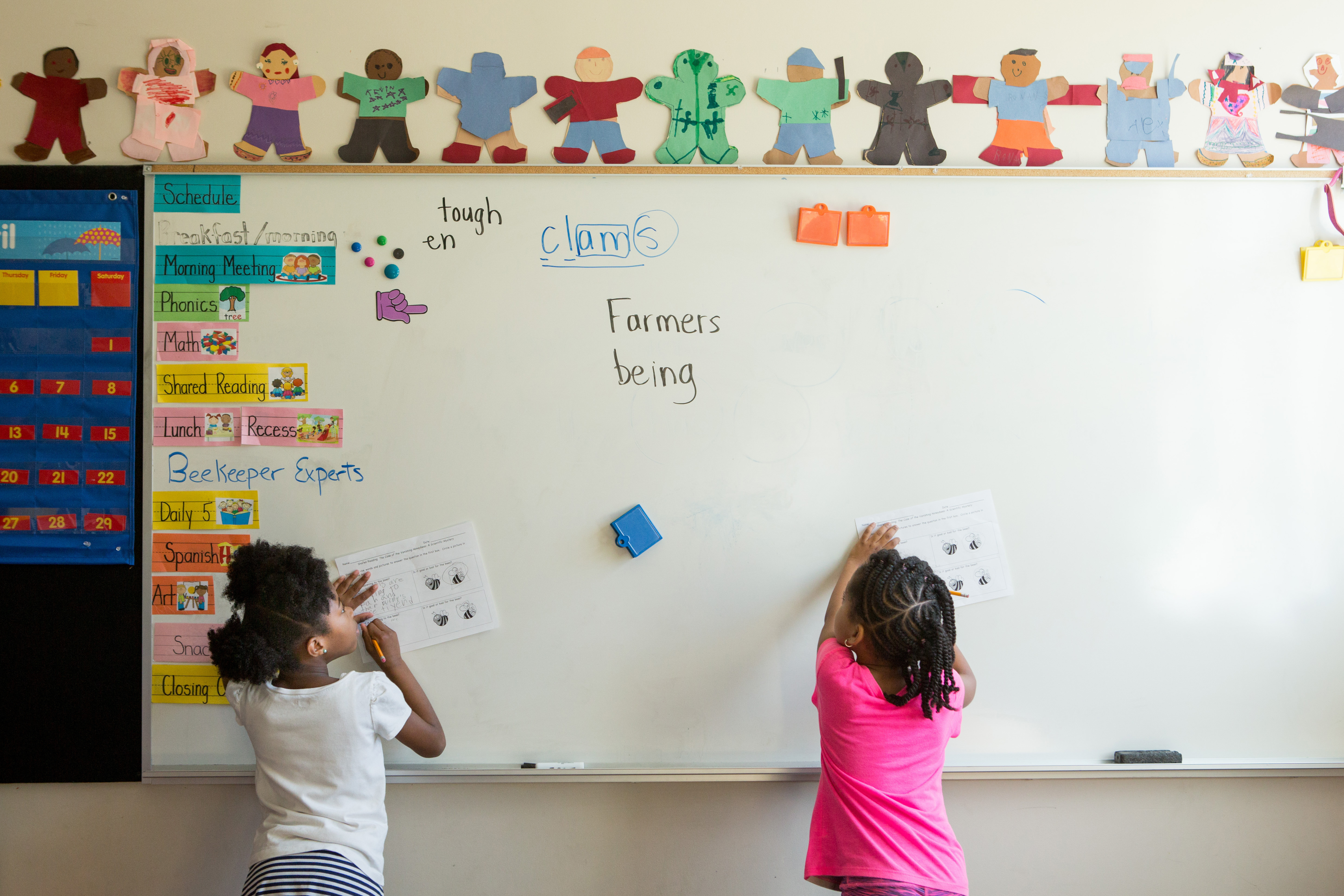 Two young girls are at a chalkboard outlined by colorful art.