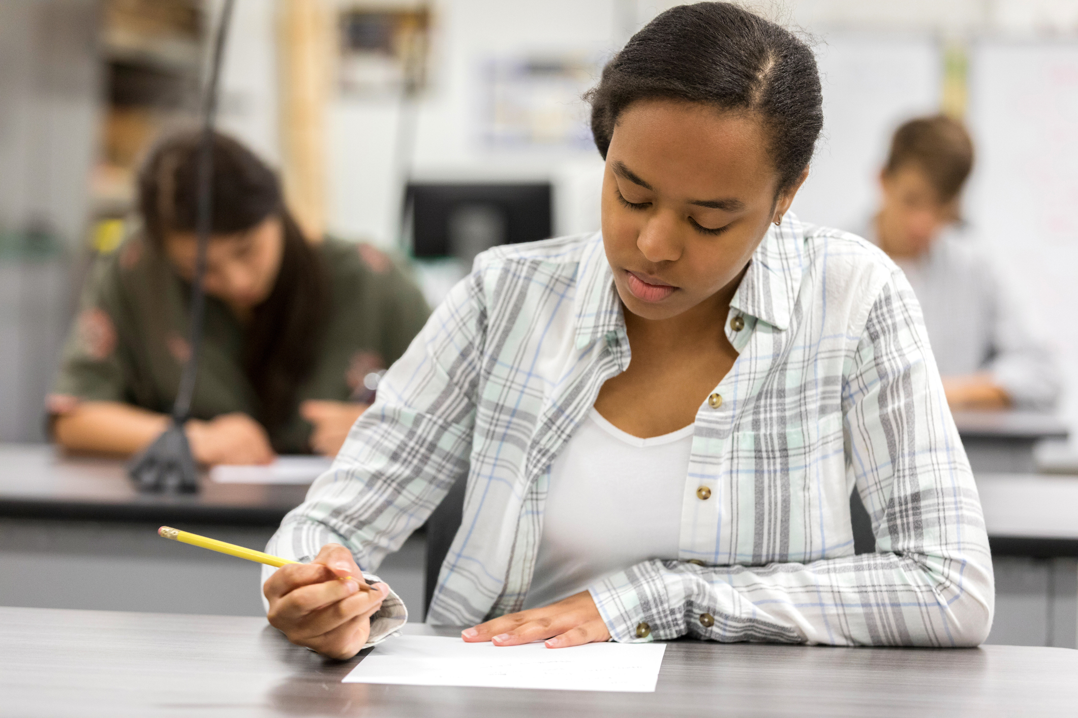 A high school student sits at a black table taking an exam with a yellow No. 2 pencil. Two students sit at black tables behind her taking an exam.