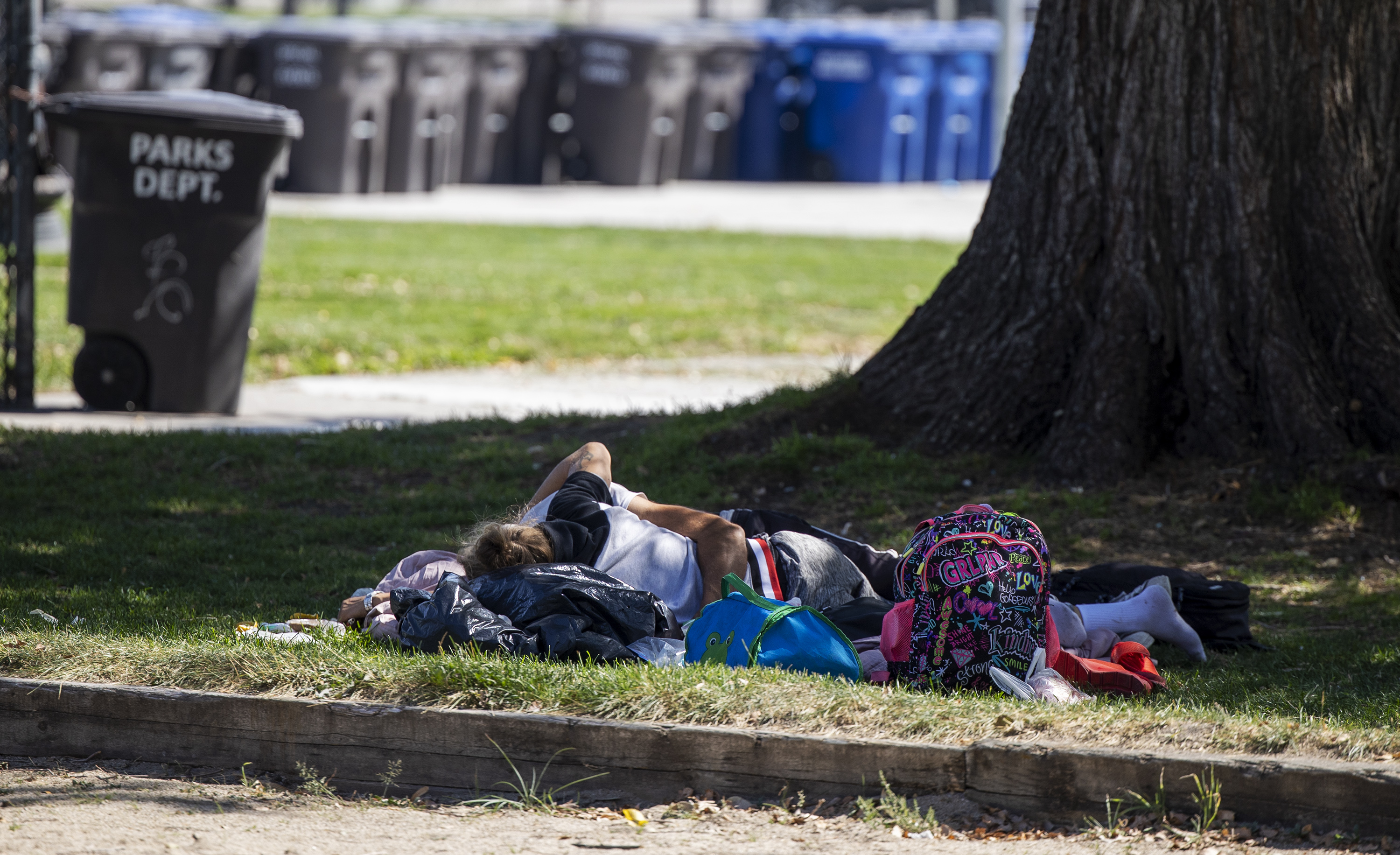 A couple lies on the grass at Pioneer Park in Salt Lake City on Tuesday, Sept. 14, 2021.The Pioneer Park Coalition on Tuesday called for immediate action to address the rise in crime and other illegal activities that go on in and around the park.